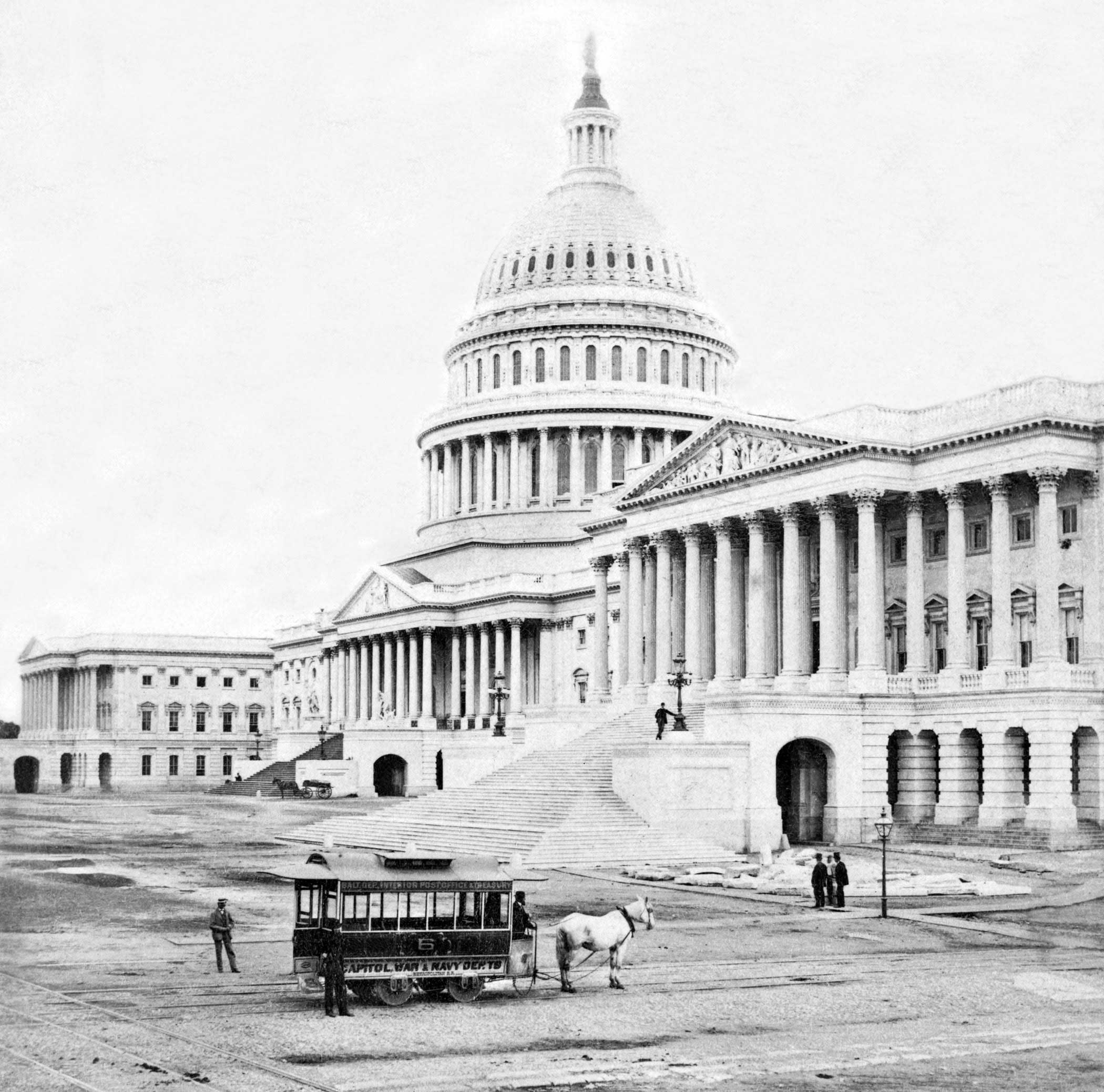 A horse-drawn tram passes by the Capitol Building circa 1875.