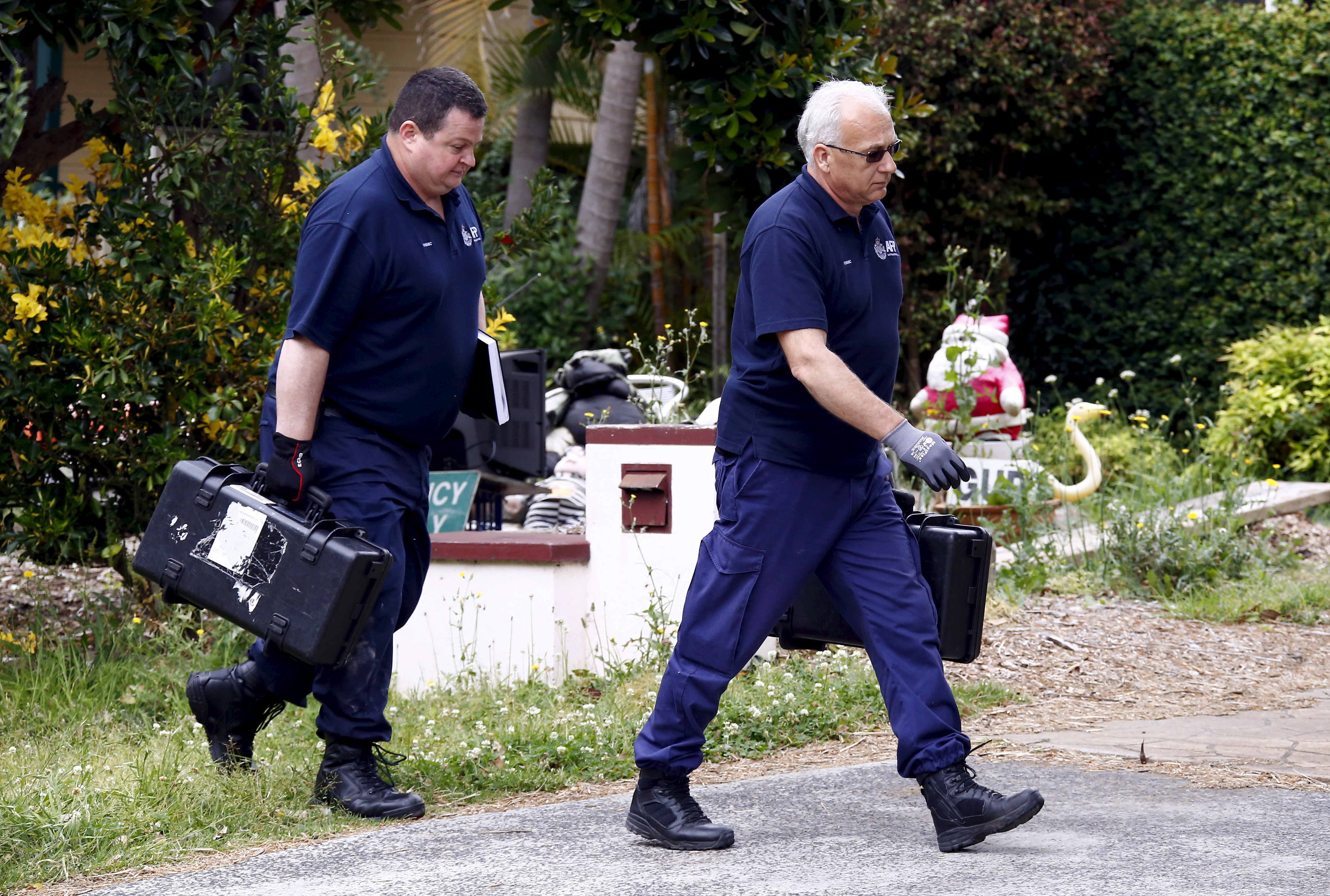 Australian federal police officers carry equipment into a house after arresting a man during early morning raids in western Sydney on Oct. 7, 2015