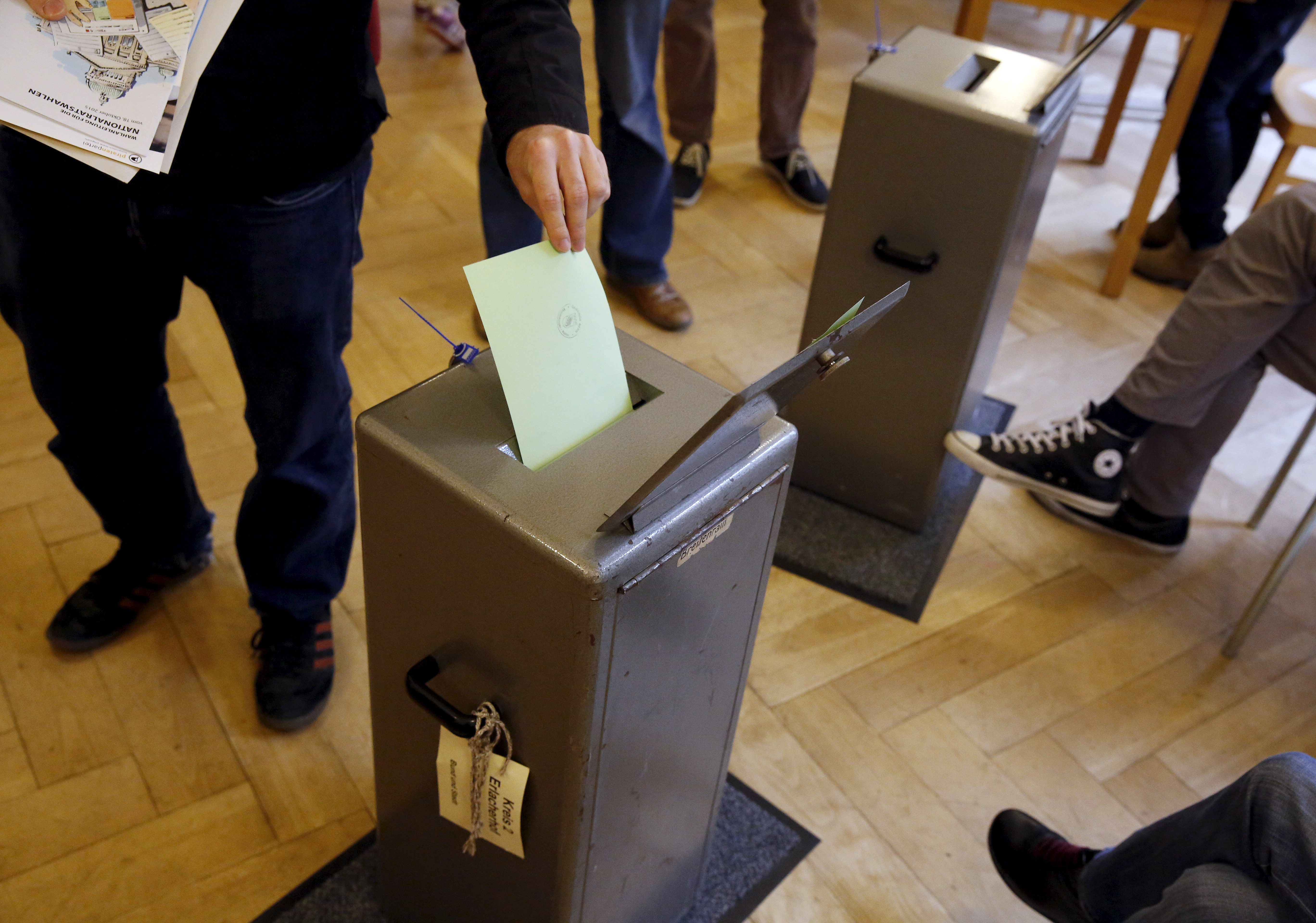People cast their vote in a school house in Bern, Switzerland, October 18, 2015.