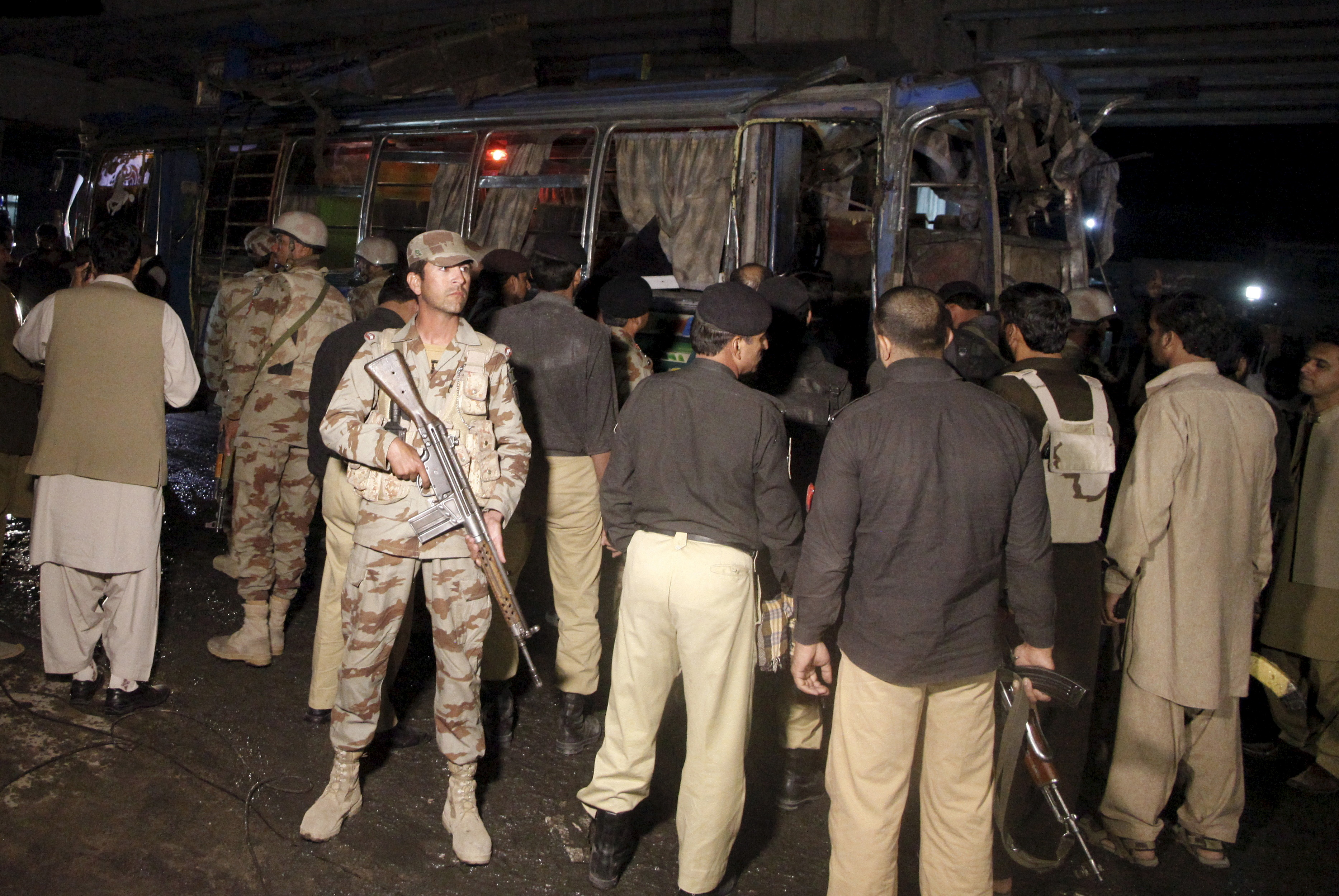 A soldier stands guard as rescue workers remove bodies from a bus after an explosion onboard as it was moving on Saryab road in Quetta, Pakistan October 19, 2015.