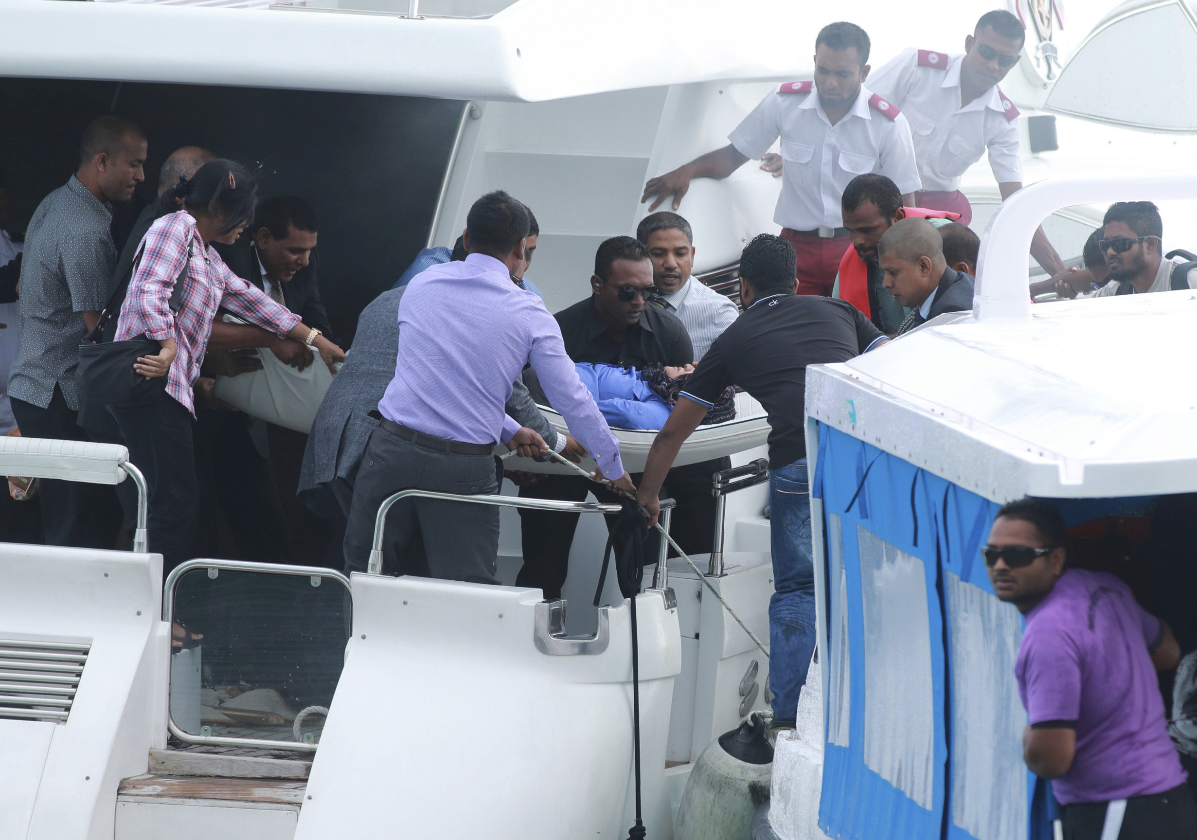 Officials carry an injured woman off the speed boat of Maldives President Abdulla Yameen (not pictured) after an explosion on board, in Male, Maldives, on Sept. 28, 2015