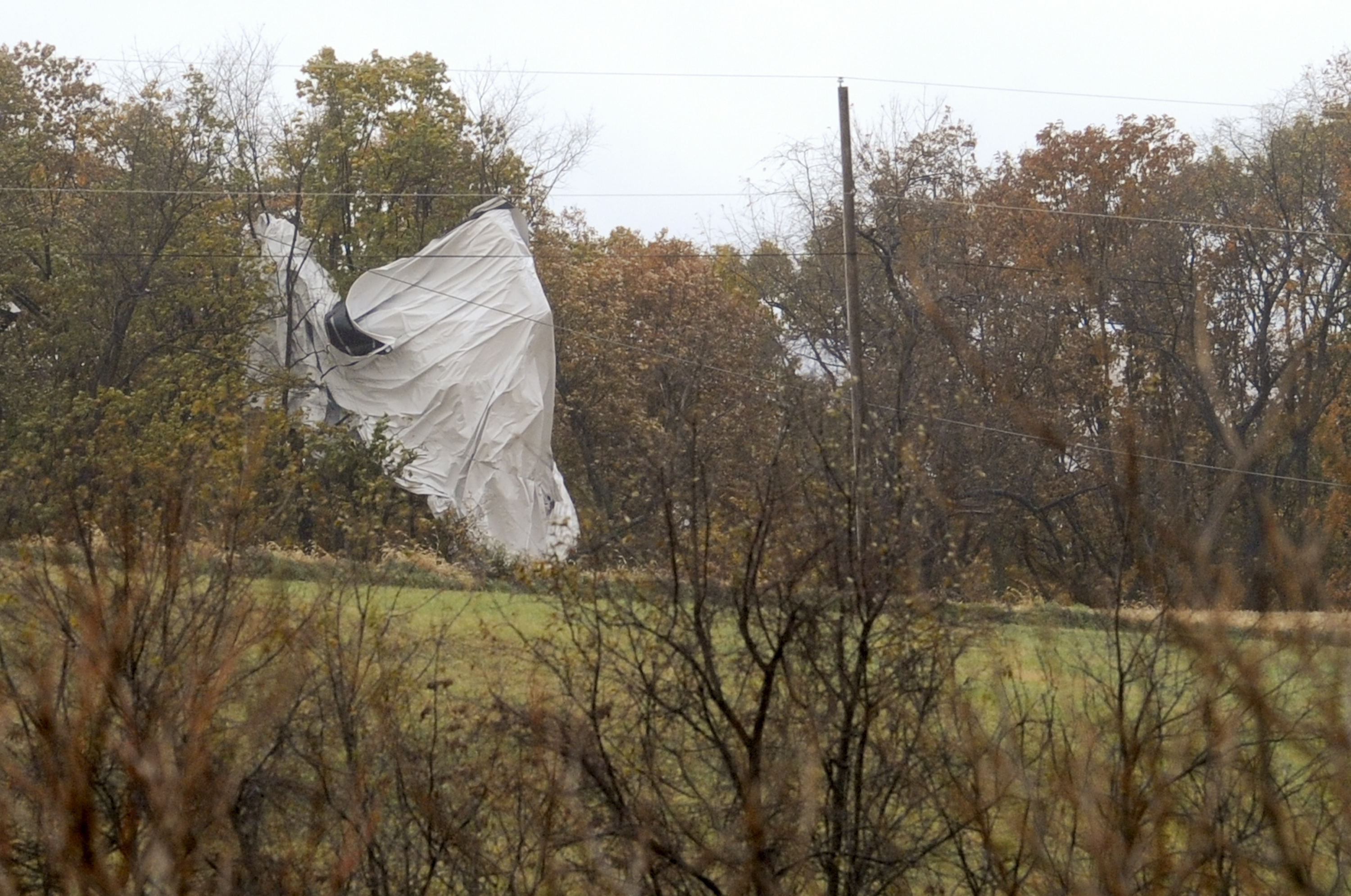 Part of an unmanned Army surveillance blimp hangs off a group of trees after crash landing near Muncy, Pa. on Oct. 28, 2015.