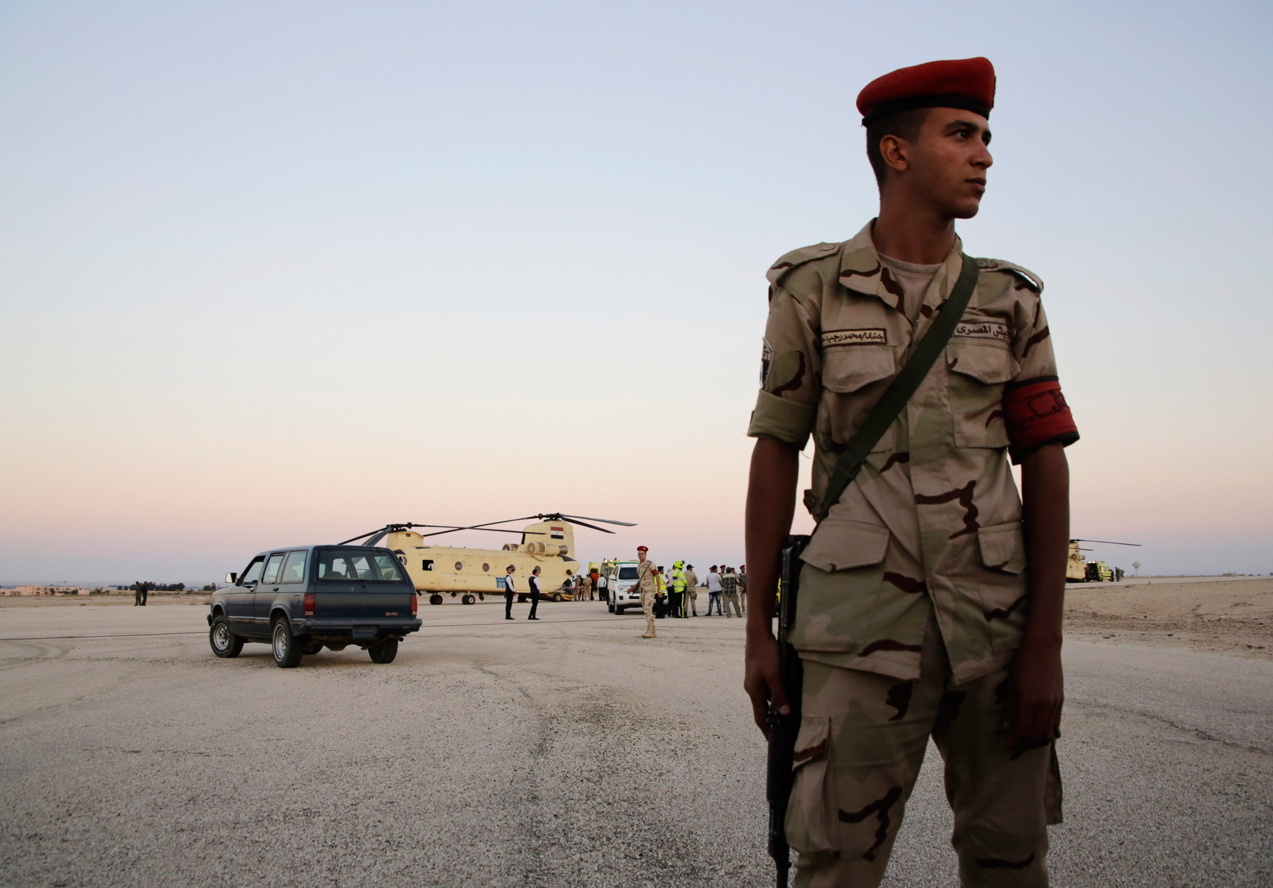 An Egyptian soldier stands guard as emergency workers unload bodies of victims from the crash of a Russian aircraft over the Sinai peninsula from a police helicopter to ambulances at the military airport in Kabrit, Egypt, on Oct. 31, 2015