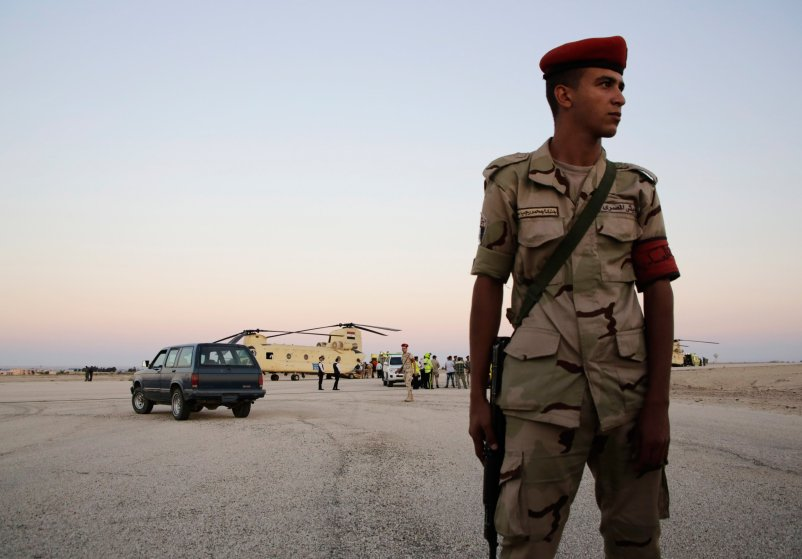 An Egyptian soldier stands guard as emergency workers unload bodies of victims from the crash of a Russian aircraft over the Sinai peninsula from a police helicopter to ambulances at Kabrit military airport, some 20 miles north of Suez, Egypt, Saturday, Oct. 31, 2015. A Russian Metrojet plane crashed Saturday morning in a mountainous region in the Sinai after taking off from Sharm el-Sheikh, killing all 224 people aboard. Officials said the pilot had reported a technical problem and was looking to make an emergency landing before radio contact with air traffic controllers went dead. (AP Photo/Amr Nabil)