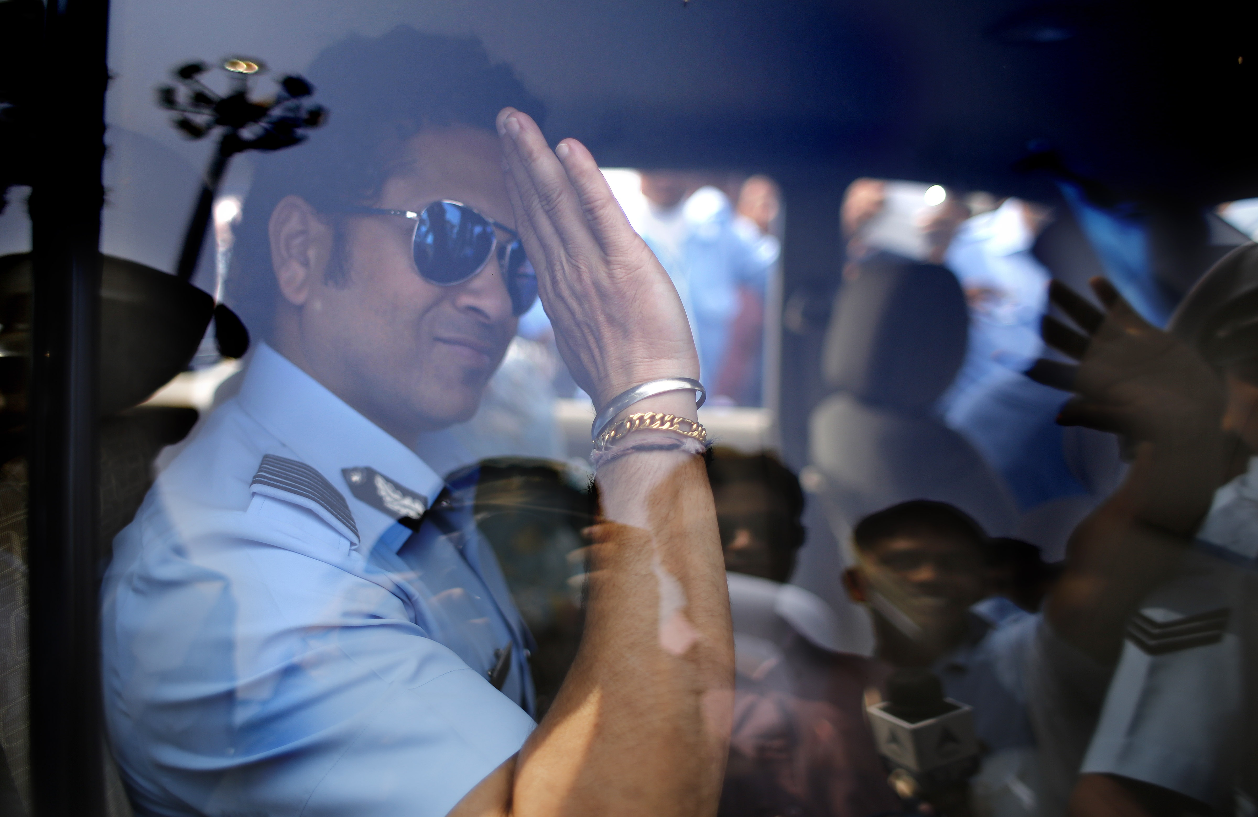 Sachin Tendulkar waves from a car on Oct. 8, 2014 in Hindon near New Delhi, India.