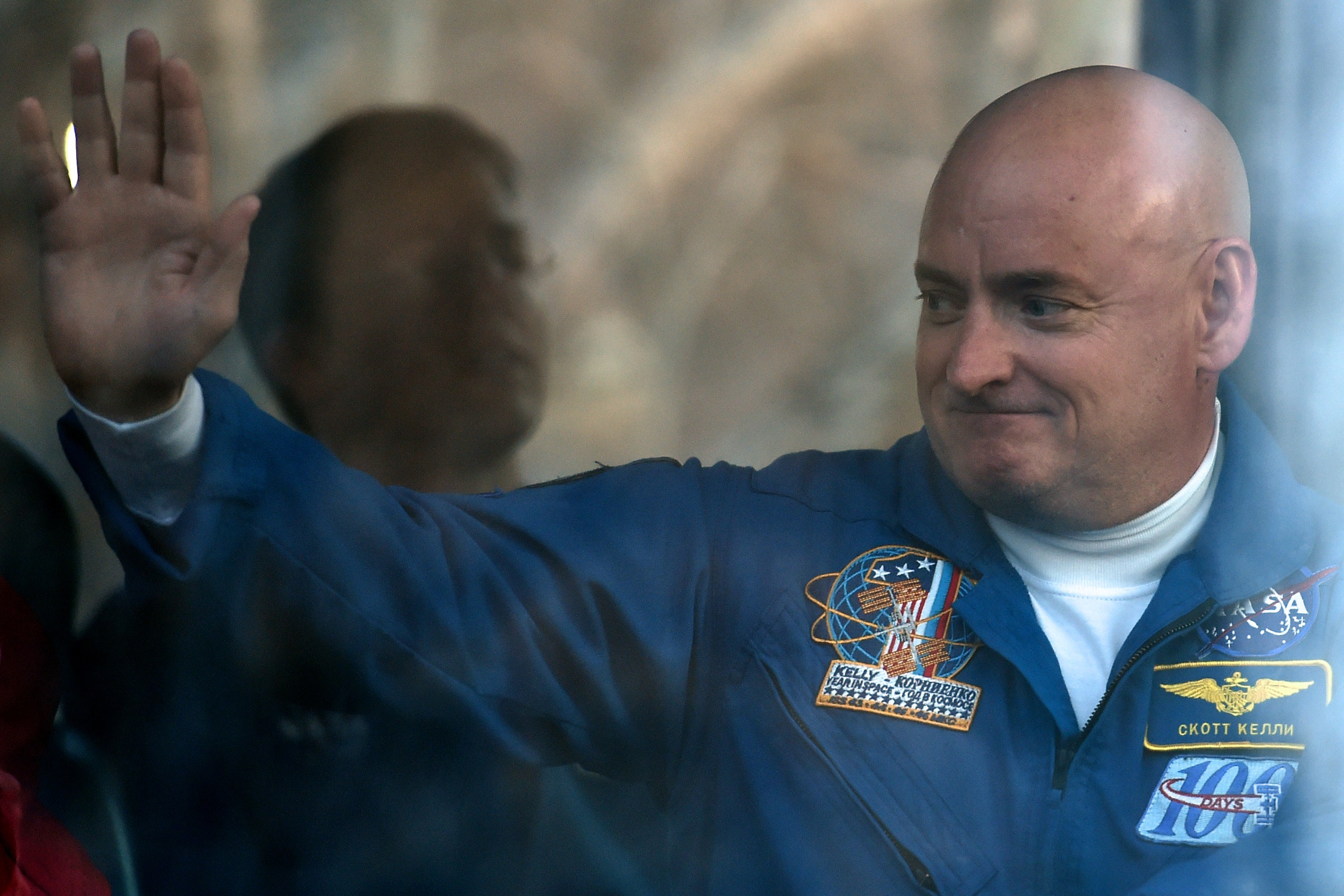 Scott Kelly waves from a bus during a sending-off ceremony in the Russian-leased Baikonur cosmodrome late on March 27, 2015.