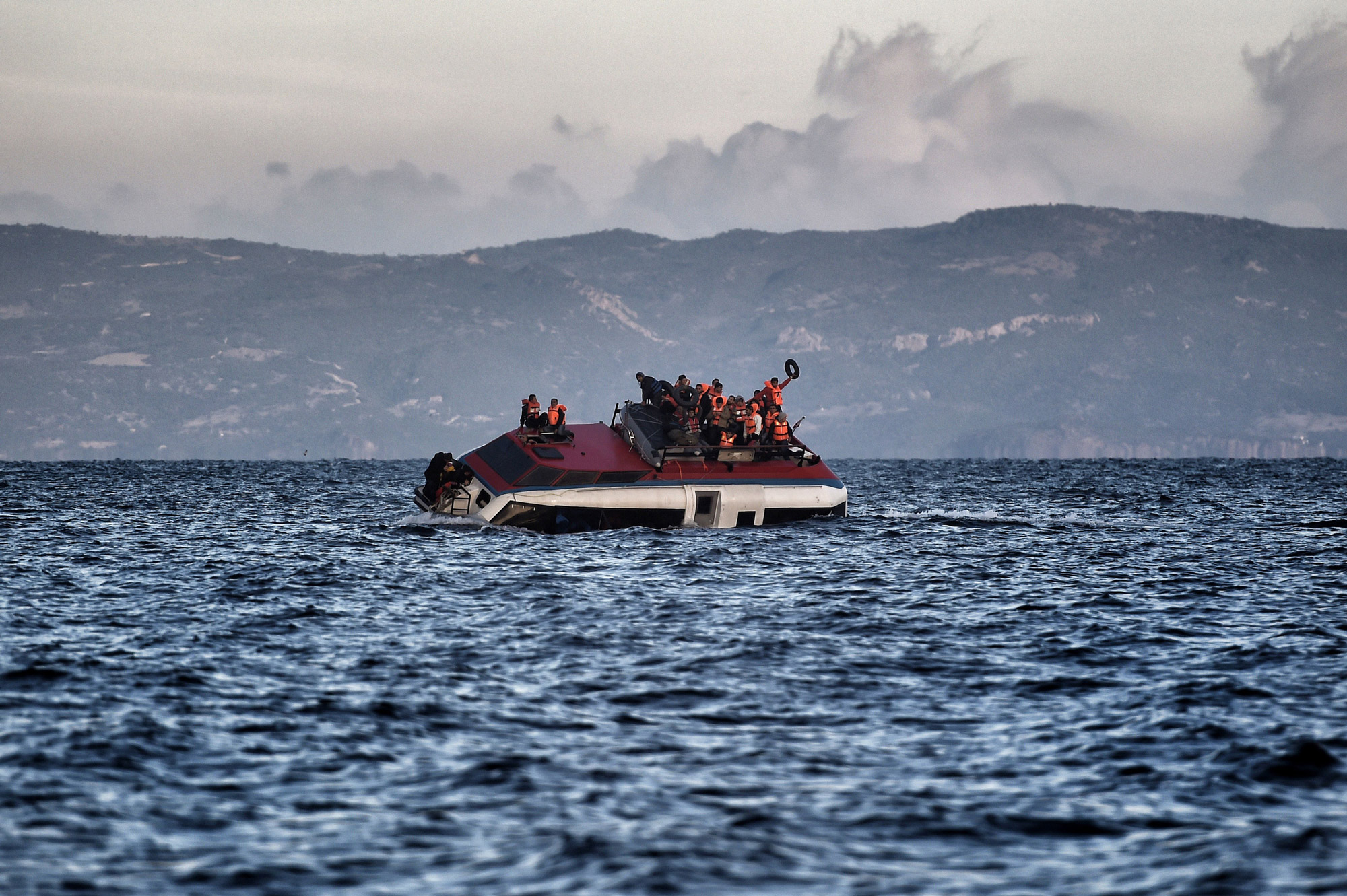 Refugees and migrants call for help as their boat is ready to sink off the Greek island of Lesbos on Oct. 30, 2015.