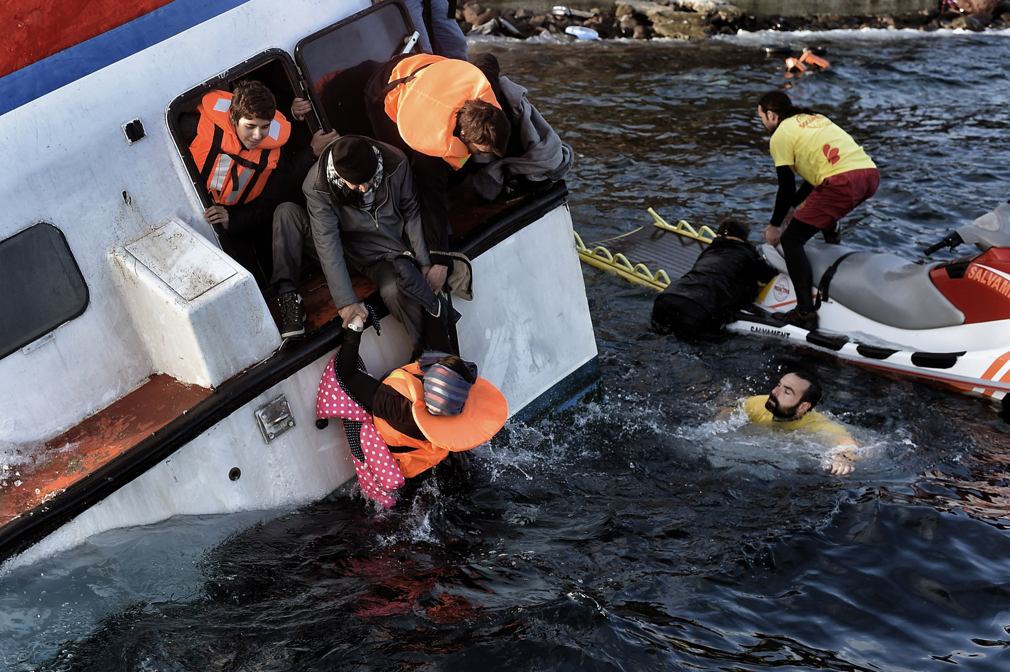 Rescue workers on a jet ski assist refugees and migrants as their boat sinks off the Greek island of Lesbos on Oct. 30, 2015.