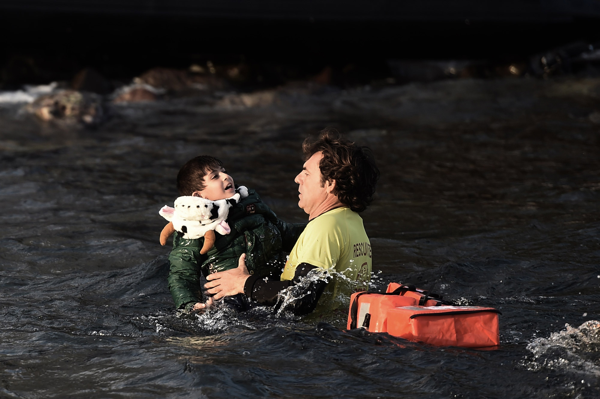 A Spanish lifeguard saves a migrant child as the boat he had boarded with other migrants and refugees sinks off the Greek island of Lesbos on Oct. 30, 2015.