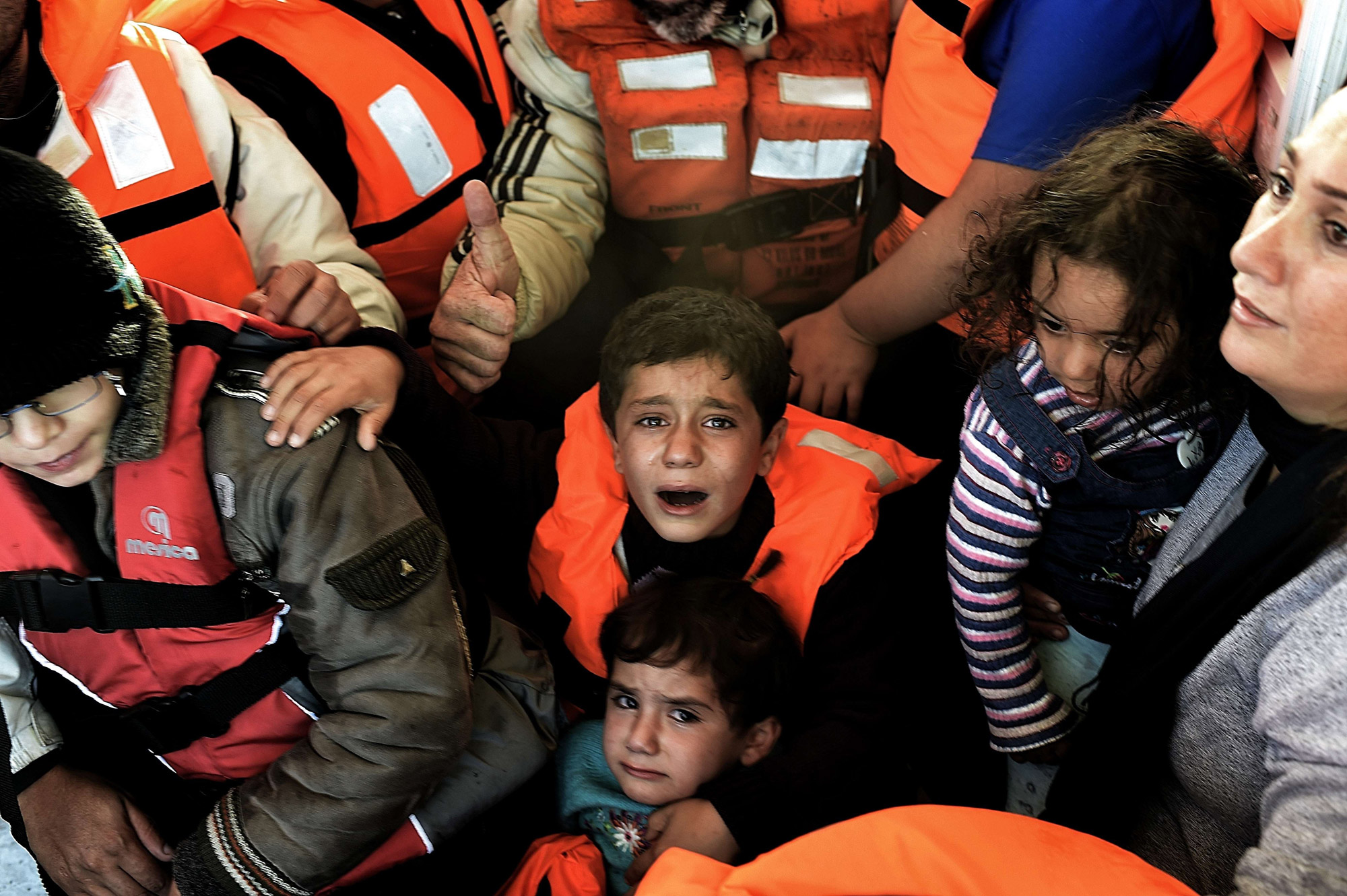 Syrian Kurdish refugees are rescued by Greek fishermen as the boat they had boarded sinks off the Greek island of Lesbos on Oct. 30, 2015.