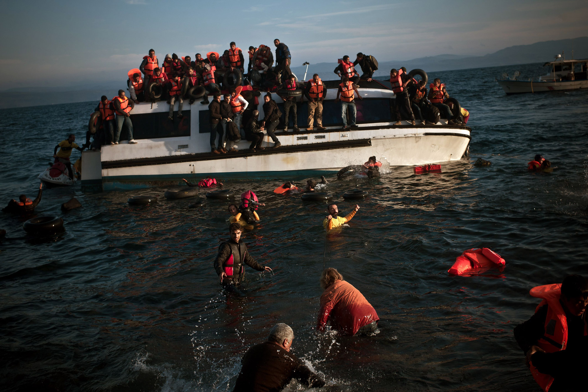 Refugees and migrants react as their boat sinks off the Greek island of Lesbos on Oct. 30, 2015.
