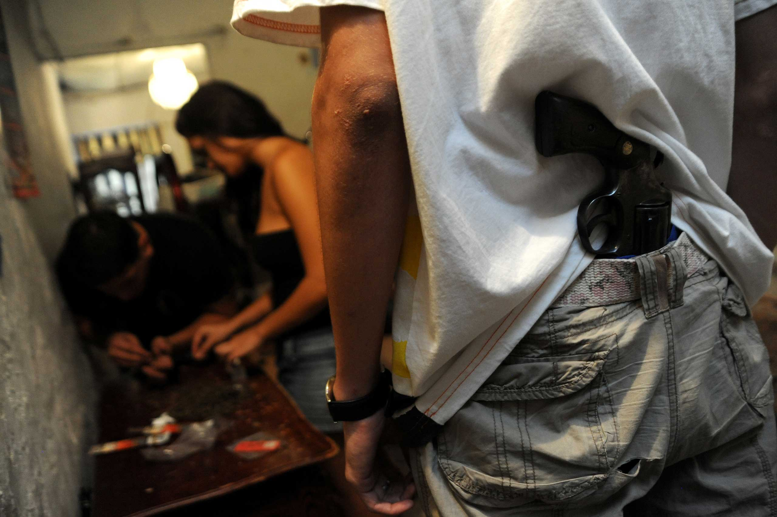 Hitman Gustavo monitors a female member of Medellin based drug cartel Los Sebastianos, as she prepares marijuana, in Comuna 3, a poor neighborhood in Medellin, Colombia.
