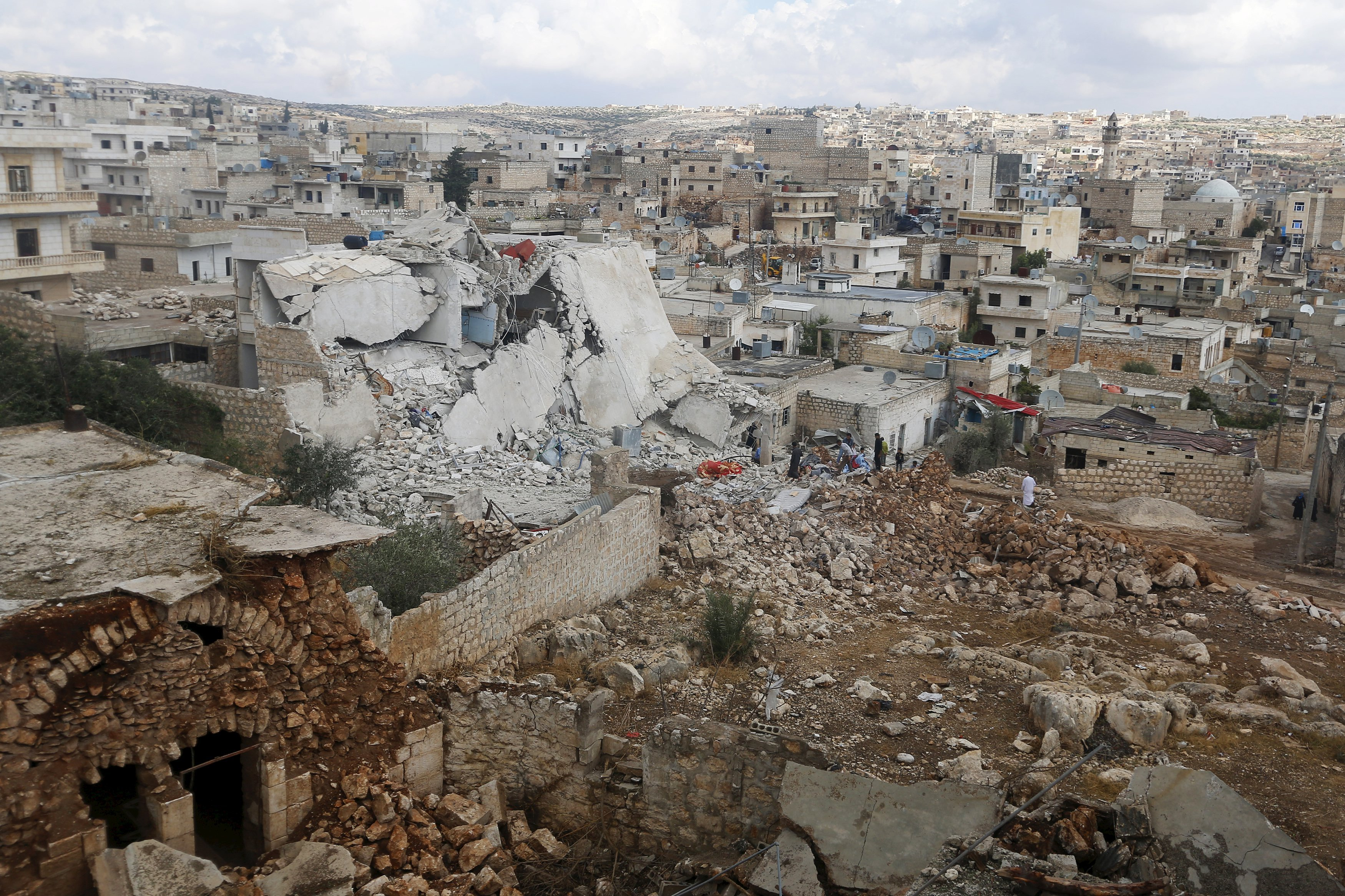 People inspect a site hit by what residents said were airstrikes carried out by the Russian air force in the town of Darat Izza in Aleppo's countryside on Oct. 7, 2015.