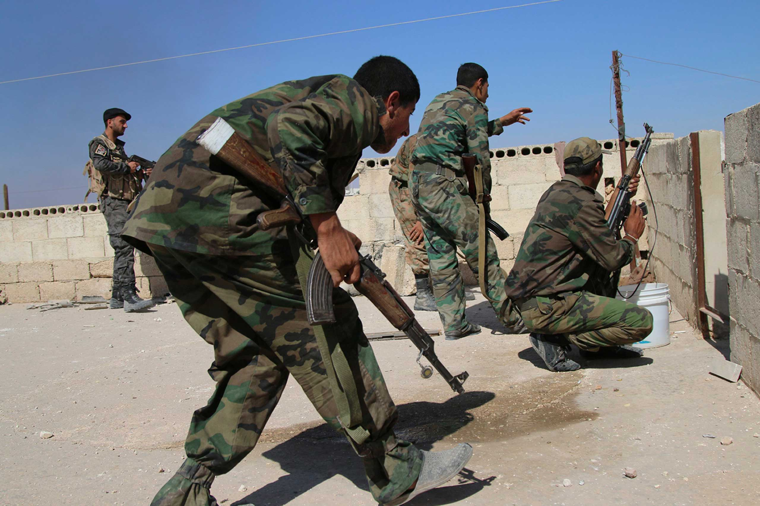 Syrian soldiers fire repelling an attack in Achan, Hama province, Syria,  Oct. 11, 2015.