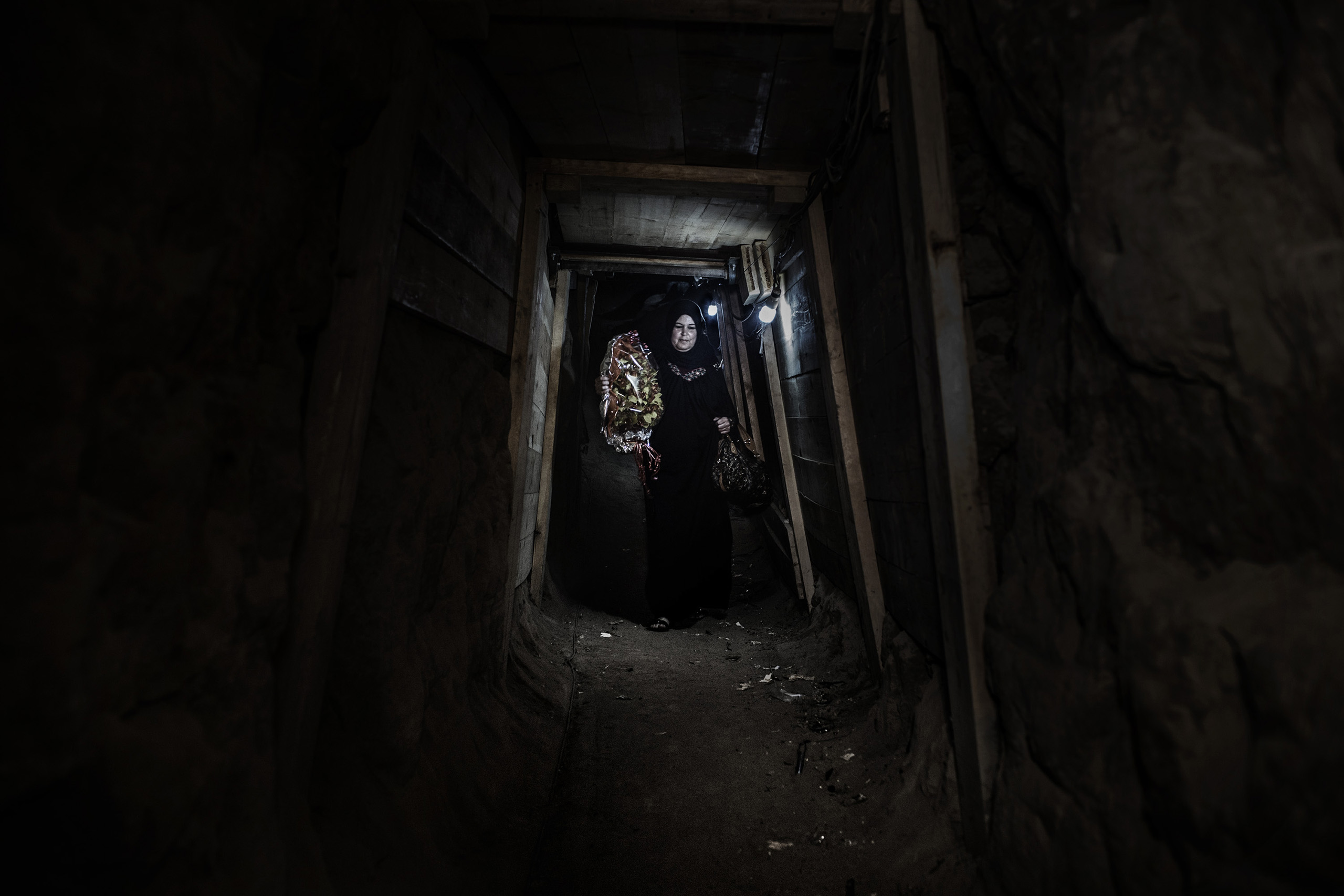 A woman in Gaza, without a travel permit, passes through  an underground tunnel on her way to a party in Egypt, carrying a bouquet of flowers.