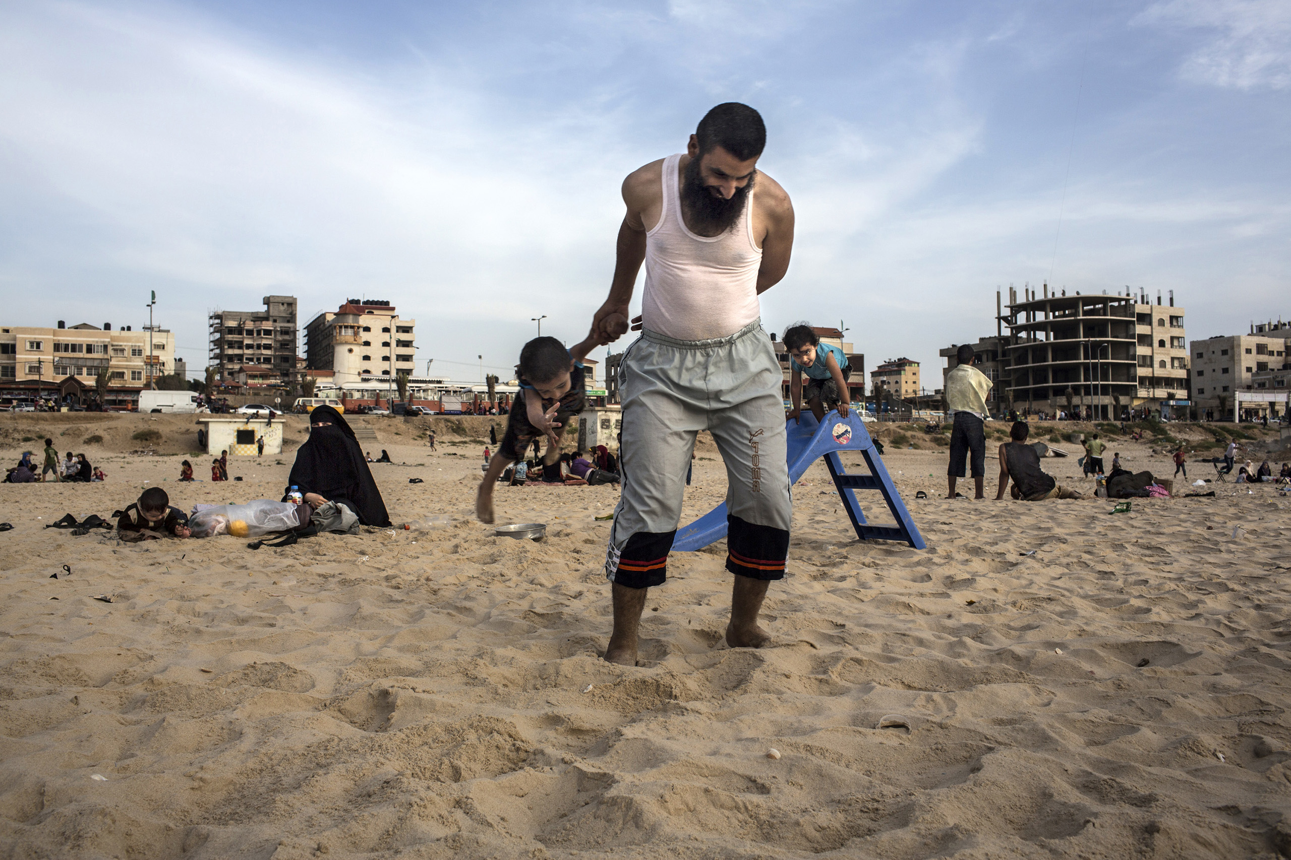 A father plays with his son at the beach, a typical scene on Friday afternoons in Gaza.