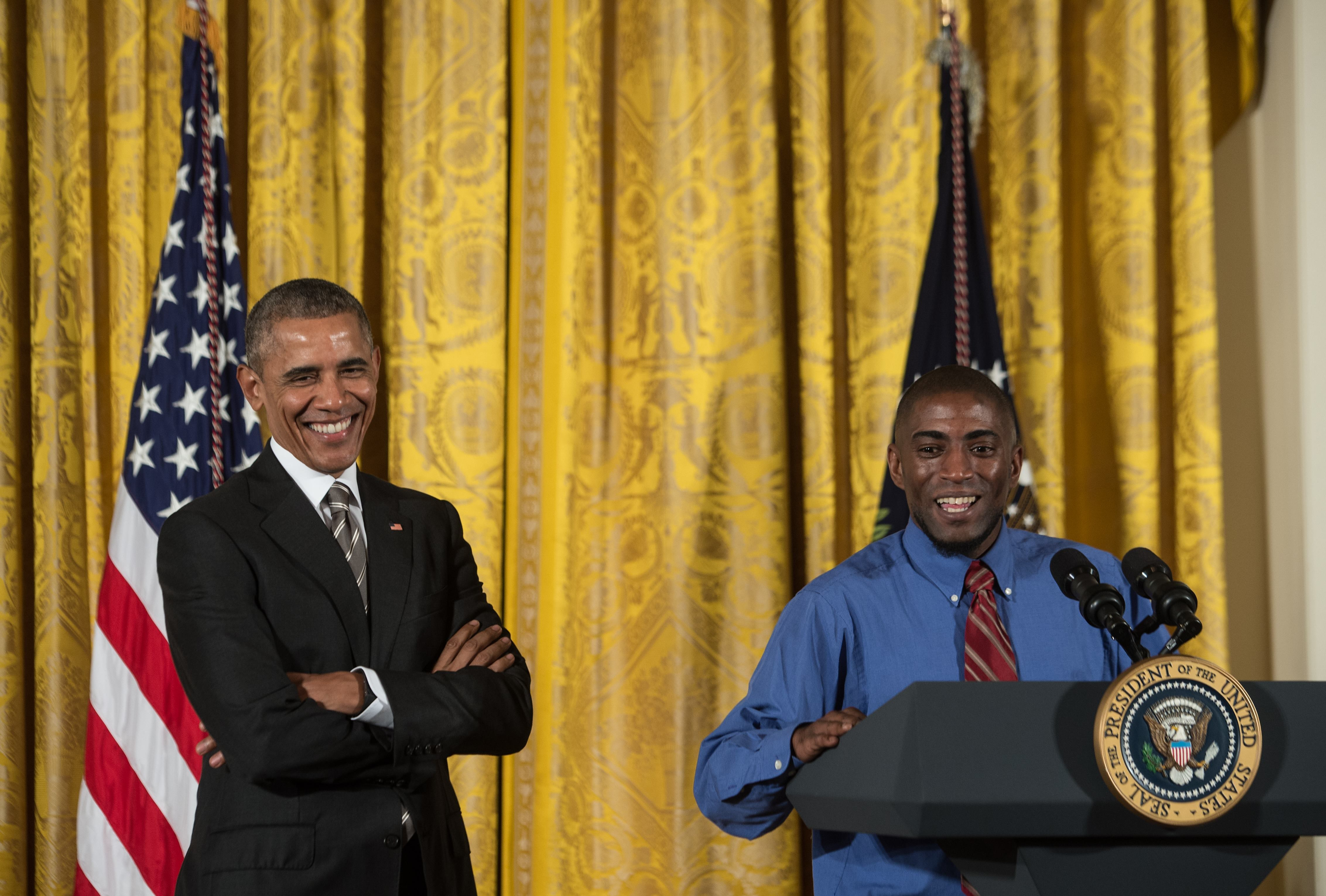 US President Barack Obama (L) smiles as he is introduced by fast food worker Terrence Wise at the Summit on Worker Voice at the White House in Washington, DC, on Oct. 7, 2015.