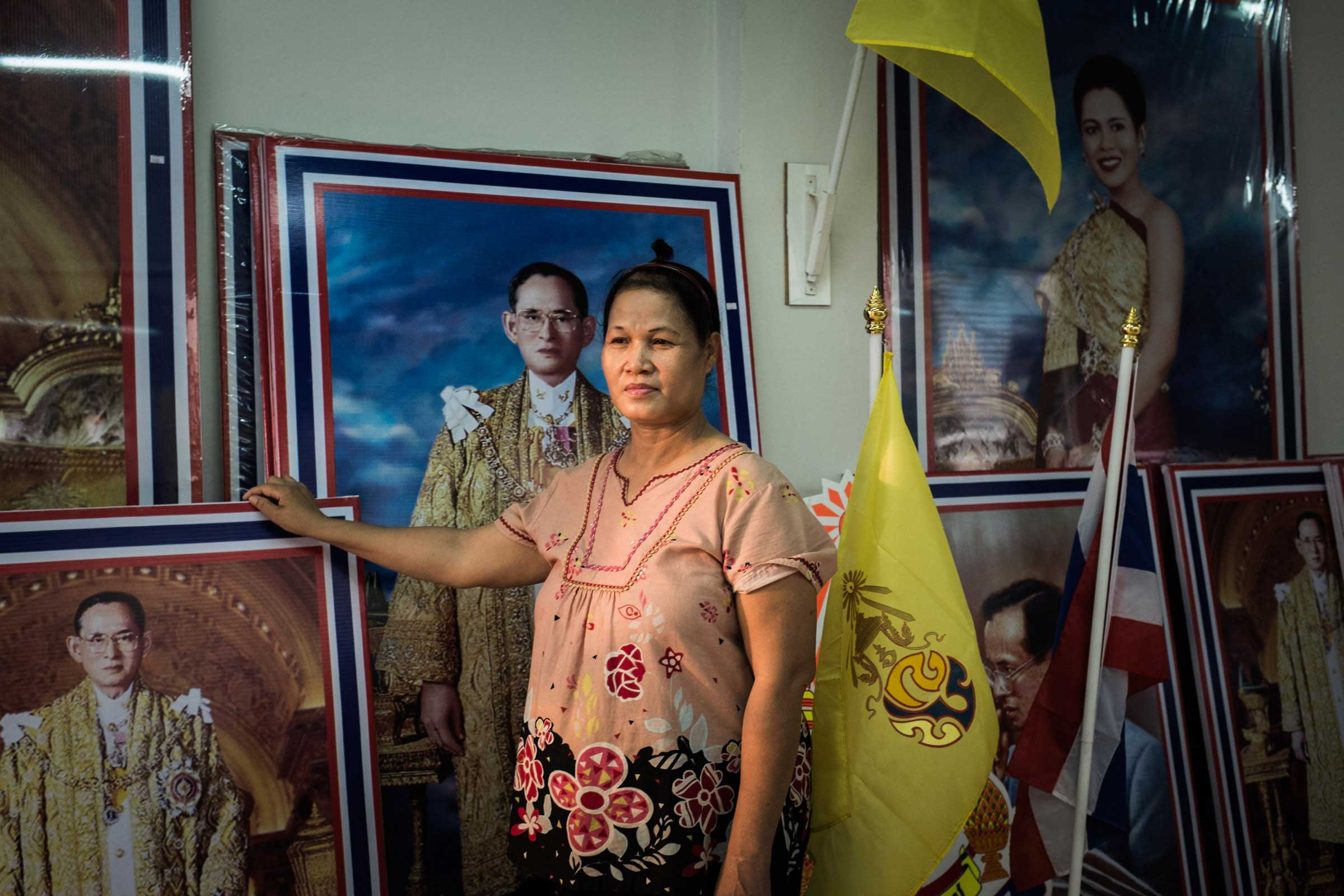 A shopkeeper poses before portraits of King Bhumibol in a store that sells only royal and national merchandise, Bangkok, Nov. 2014.