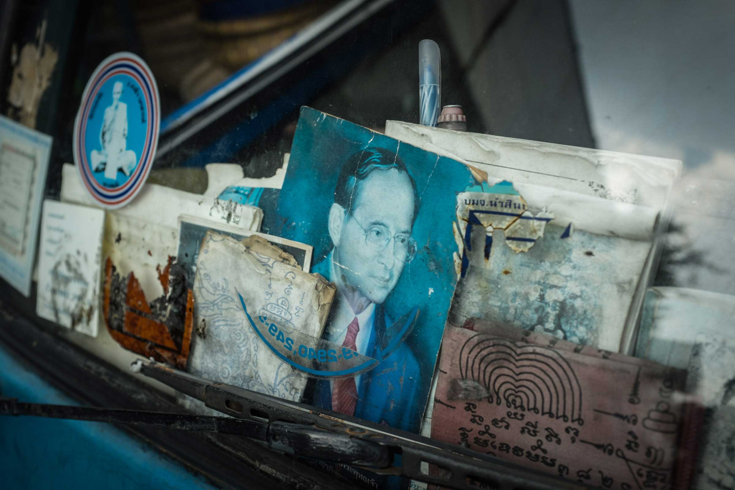 A portrait of the beloved and revered King Bhumibol Adulyadej of Thailand, also known as Rama IX, is visible from the rear windshield of a car in Nov. 2014.