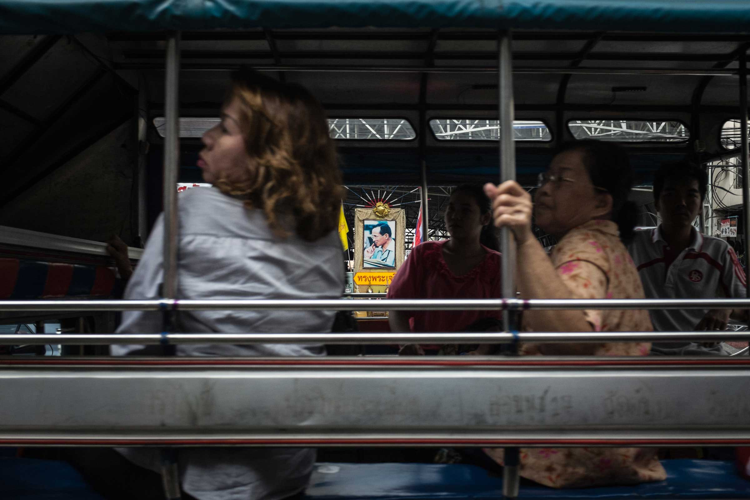 A portrait of King Bhumibol is visible through a minibus in Bangkok, Nov. 2014.
