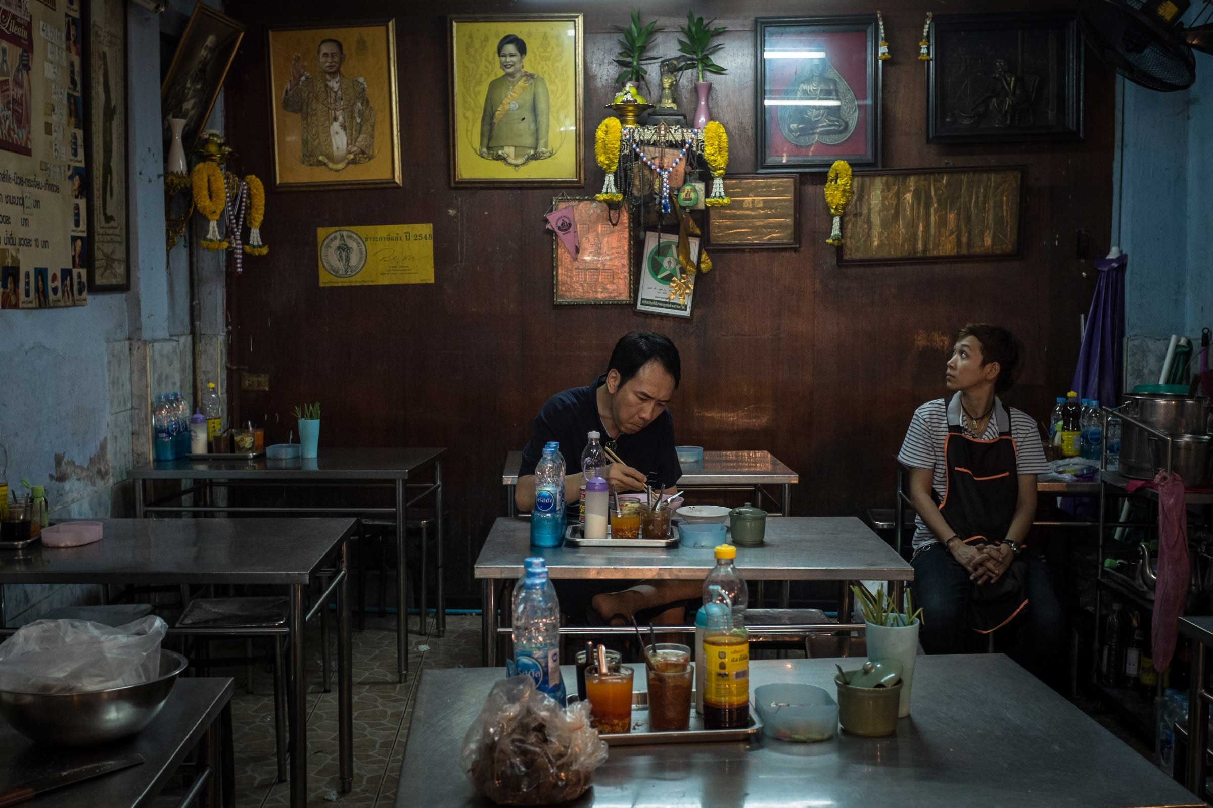 Portraits of King Bhumibol and Queen Sirikit hang in a noodle shop in Bangkok, Nov. 2014.