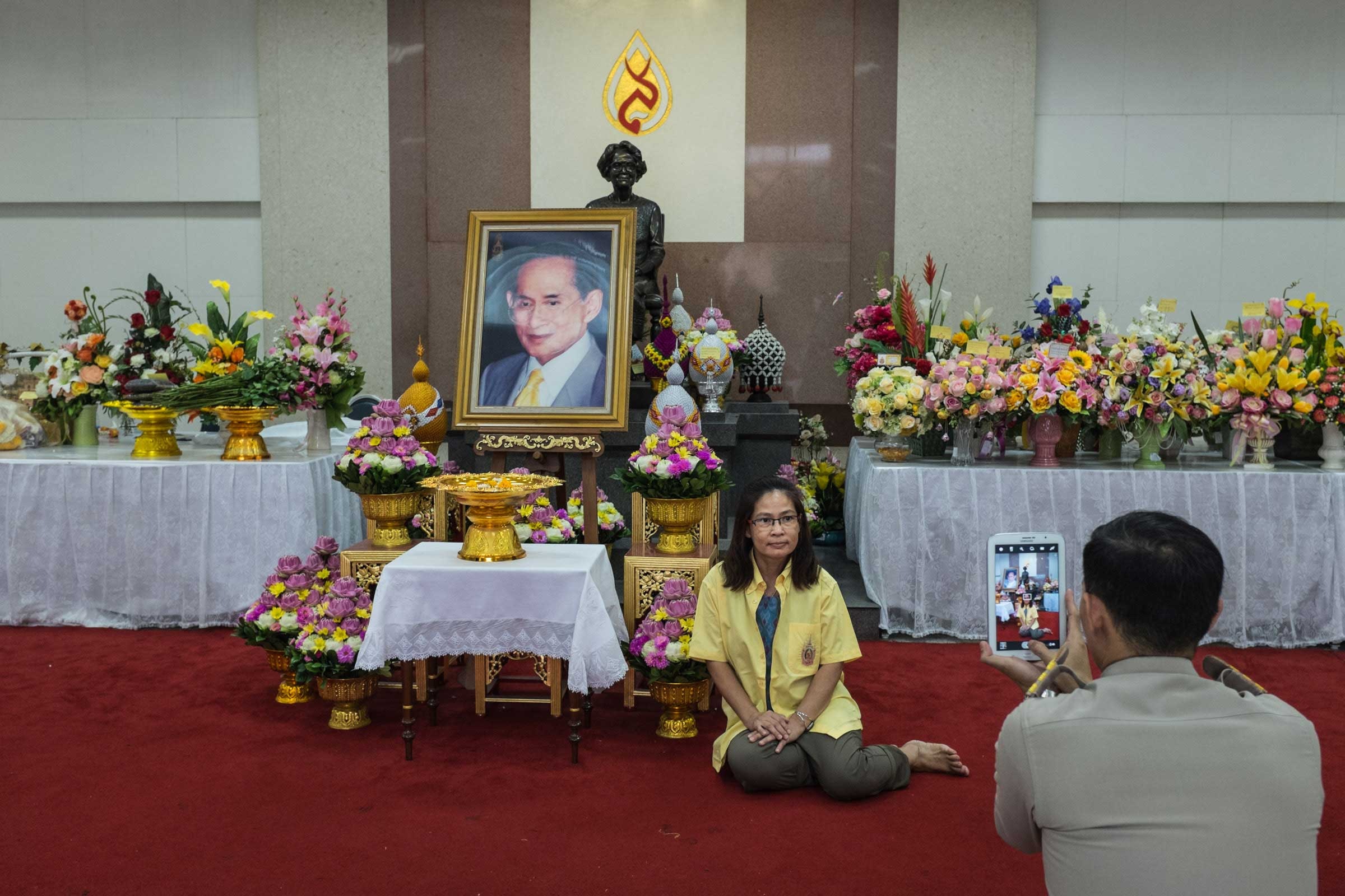 A Thai military officer photographs a woman who has come to pay respects to King Bhumibol at Siriraj Hospital in Bangkok, Nov. 2014. Every day, people visit his shrine to pray for his health.