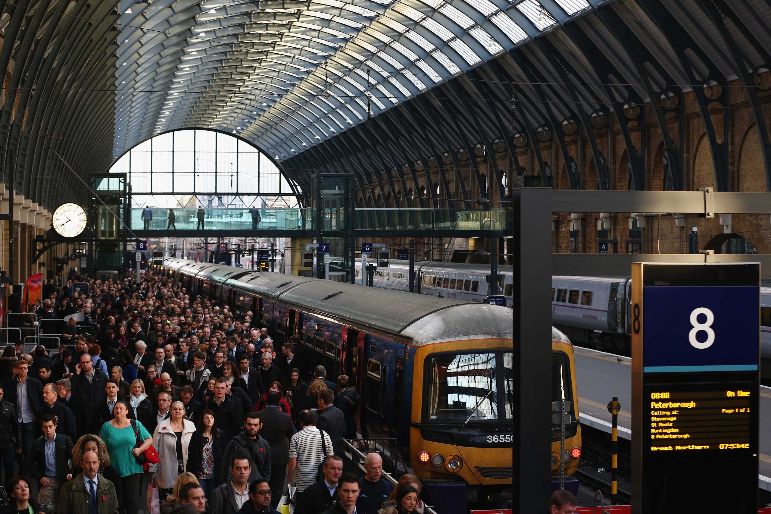 Passengers disembark a train at King's Cross station in London.