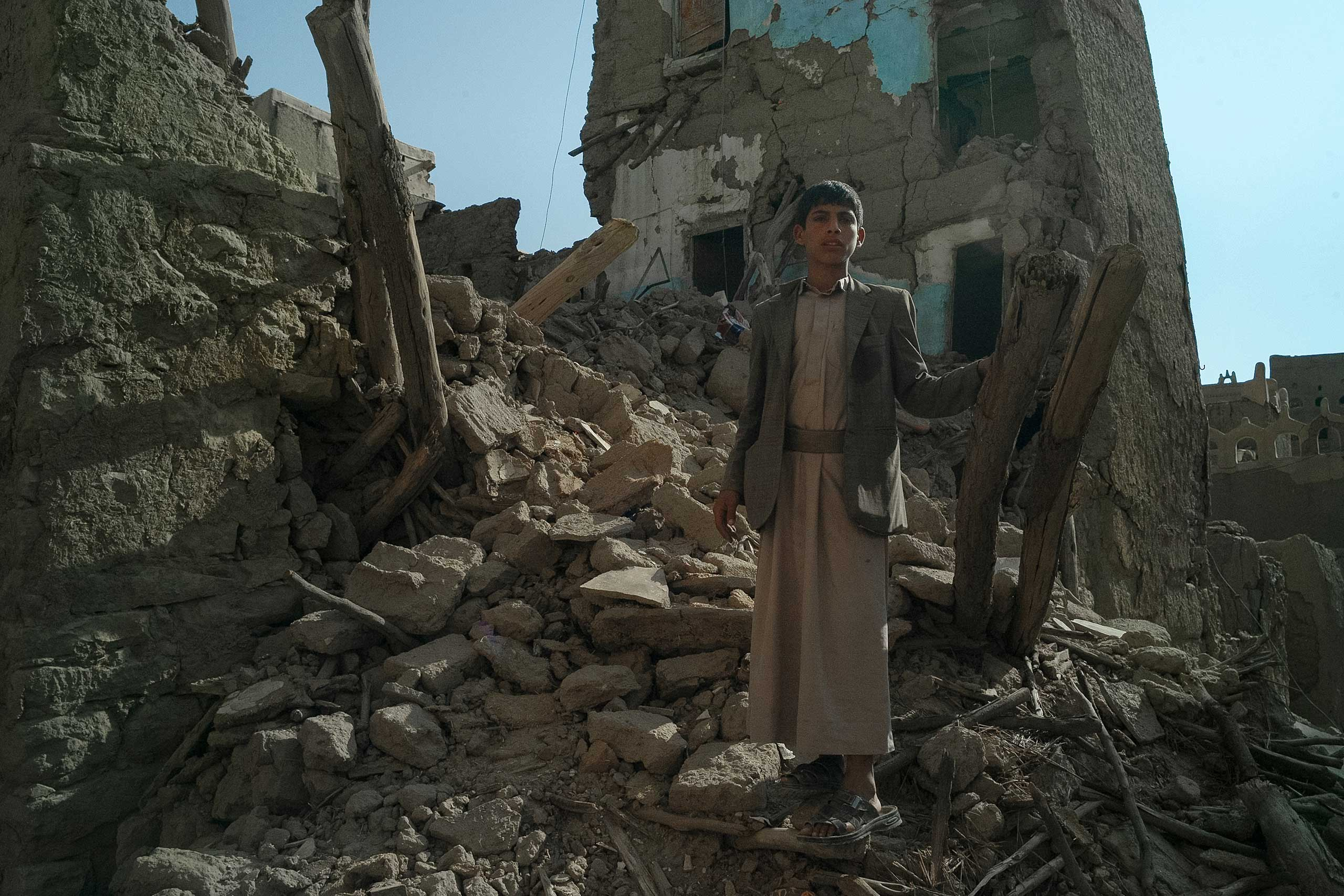 Abdul Bassat, 12, stands in the wreckage of his aunt's former home. The neighborhood of ancient mud brick  buildings on the outskirts of Saada city was destroyed by several Saudi-led airstrikes in May, 2015. Saada province is the stronghold of the Houthi rebellion movement, Aug. 2015.