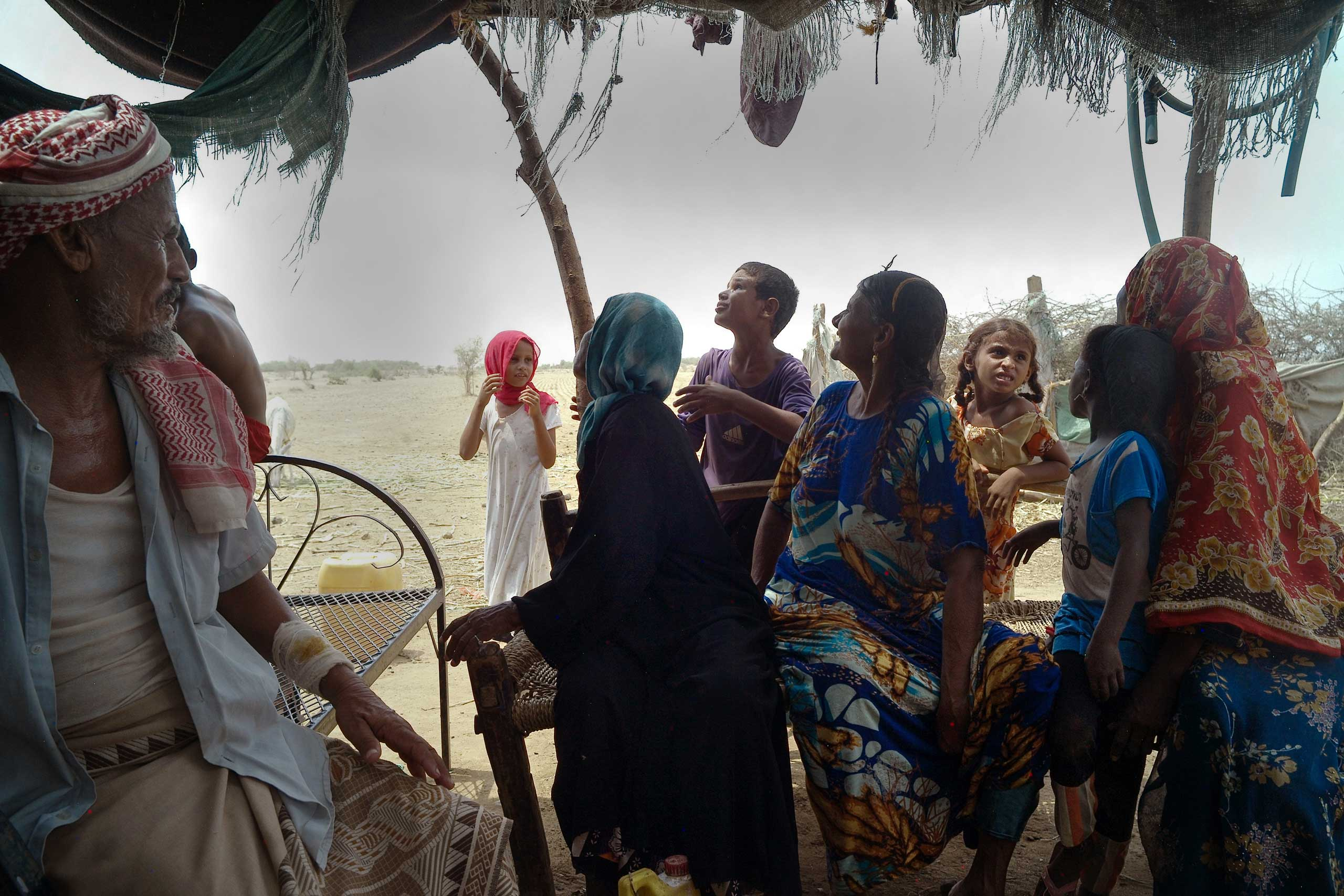 Displaced people (IDPs) from the city of Haradh react as they hear the sound of an airplane above their  camp in the Hajjah governorate, Aug. 2015.