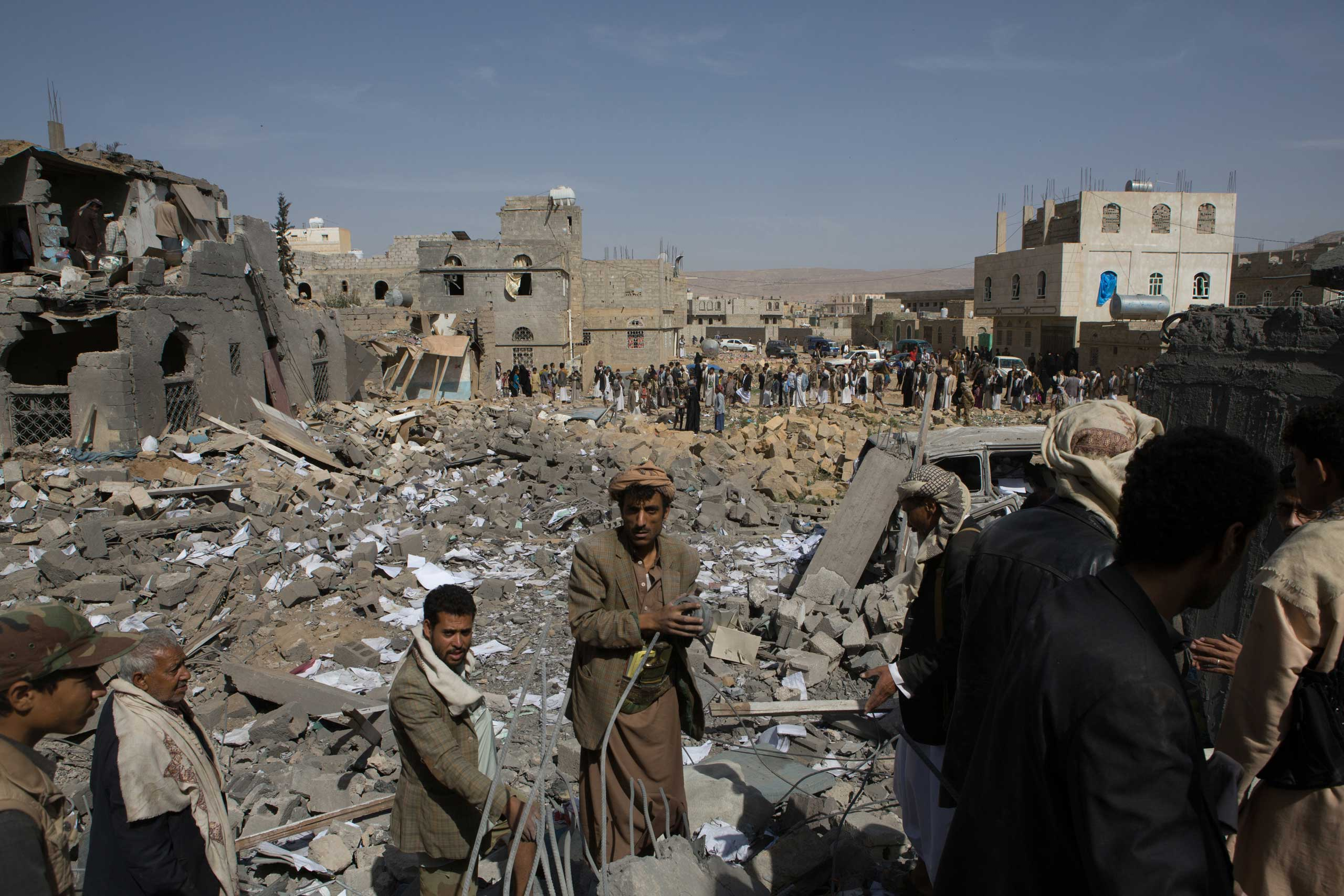 Men stand on the rubble of a building destroyed by a Saudi airstrike in Amran, 50 km from the capital city Sanaa. Eleven civilians were killed, Aug. 19, 2015.