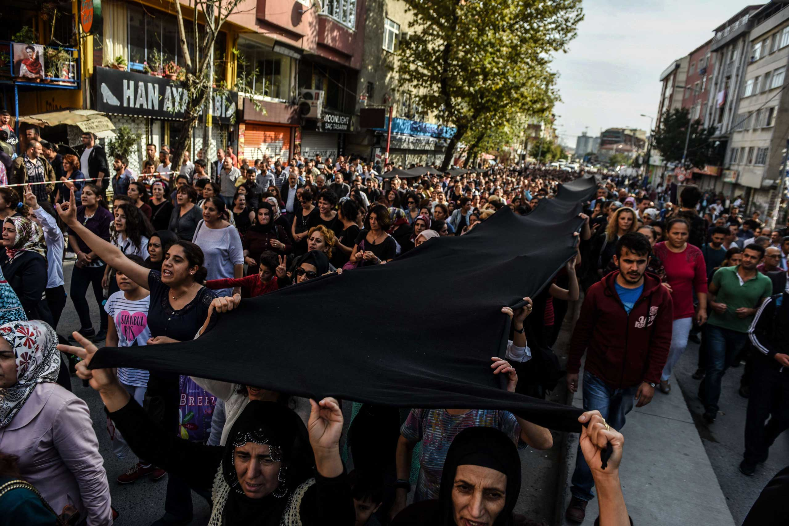People march behind a funeral vehicle carrying the coffin of Fatma Esen, one of the victims of the twin bombings in Ankara, during her funeral in the Gazi district of Istanbul, on Oct. 12, 2015.