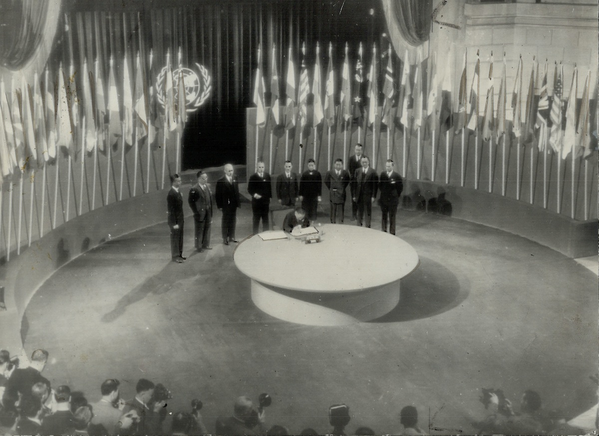 The historic Room where the United Nations security charter was signed is seen in this general view with members of the Chinese delegation lined up while Dr. W. K. Wellington Koo signs the charter for this country on June 27, 1945. The room is in the San Francisco Veterans building.