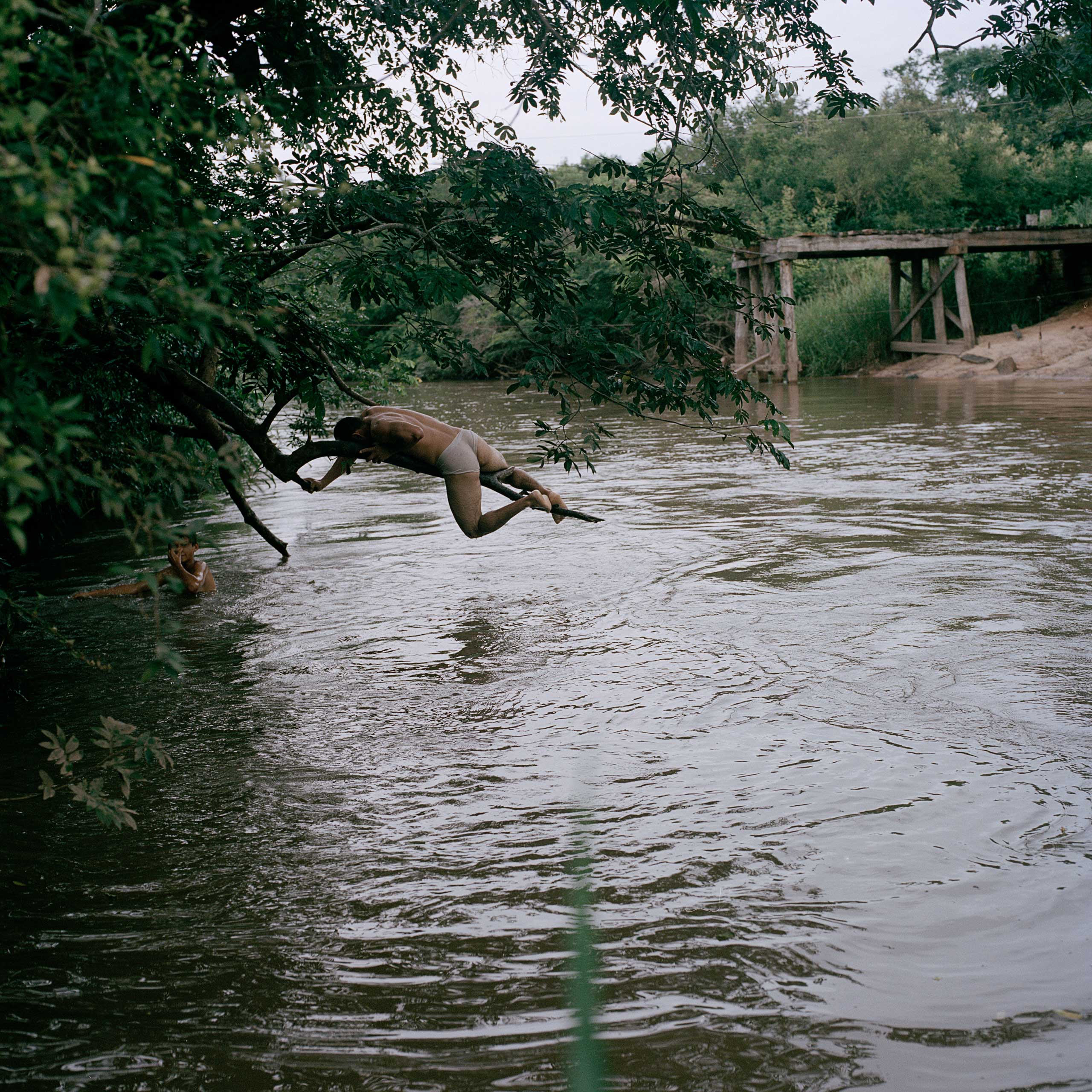 A group of teenagers swim in the river near the Tava Jopoy settlement. Although locals claim it's severely polluted, and few fishes remain, they still enjoy their time by the river.