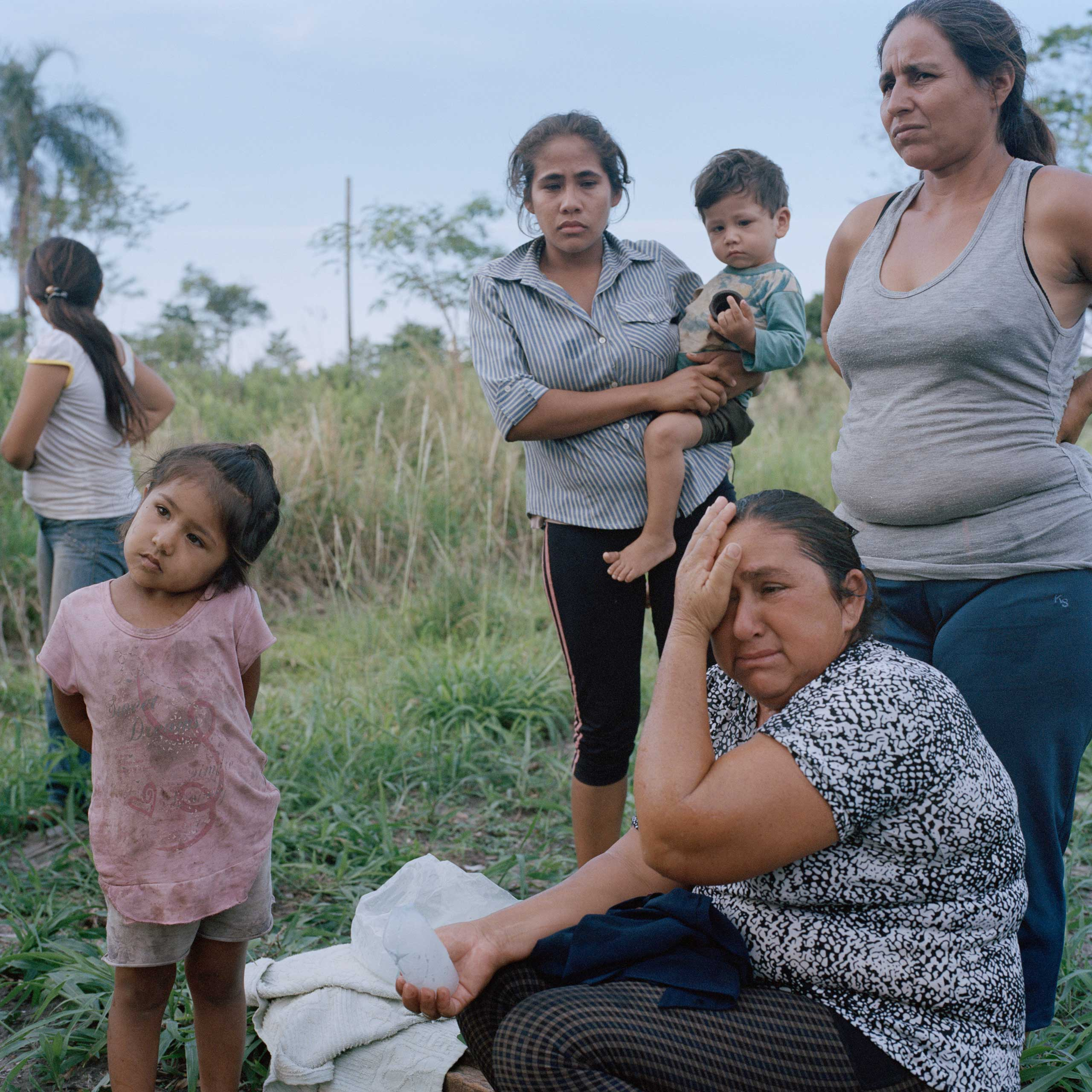 María Lina Estorales (bottom right) sobs as she explains how she and 21 other families of the small community of Guayaqui Cuá were evicted and their properties burned two days earlier. She said security men from the nearby cattle ranch together with local police officers evicted them without notice on behalf of the large-estate owner. Disputes over land ownership are a major issue in Paraguay.