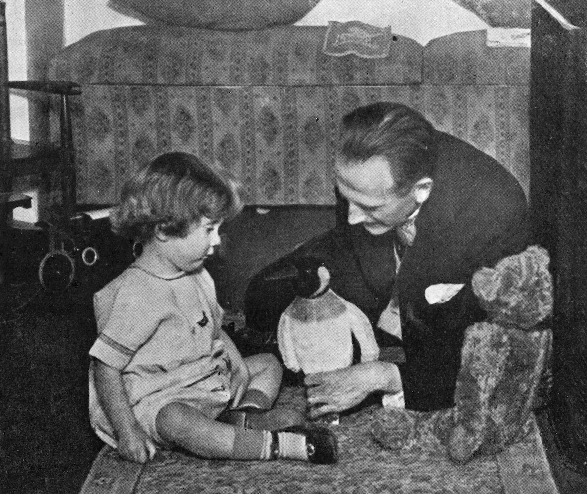 A.A. Milne and Christopher Robin Milne playing with a toy teddy bear