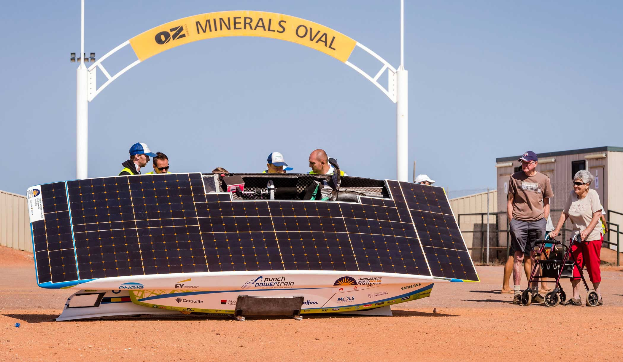 Crew members of the Belgian Punch Powertrain Solar Team standing as the car batteries are charged at Coober Pedy on Oct. 21, 2015.