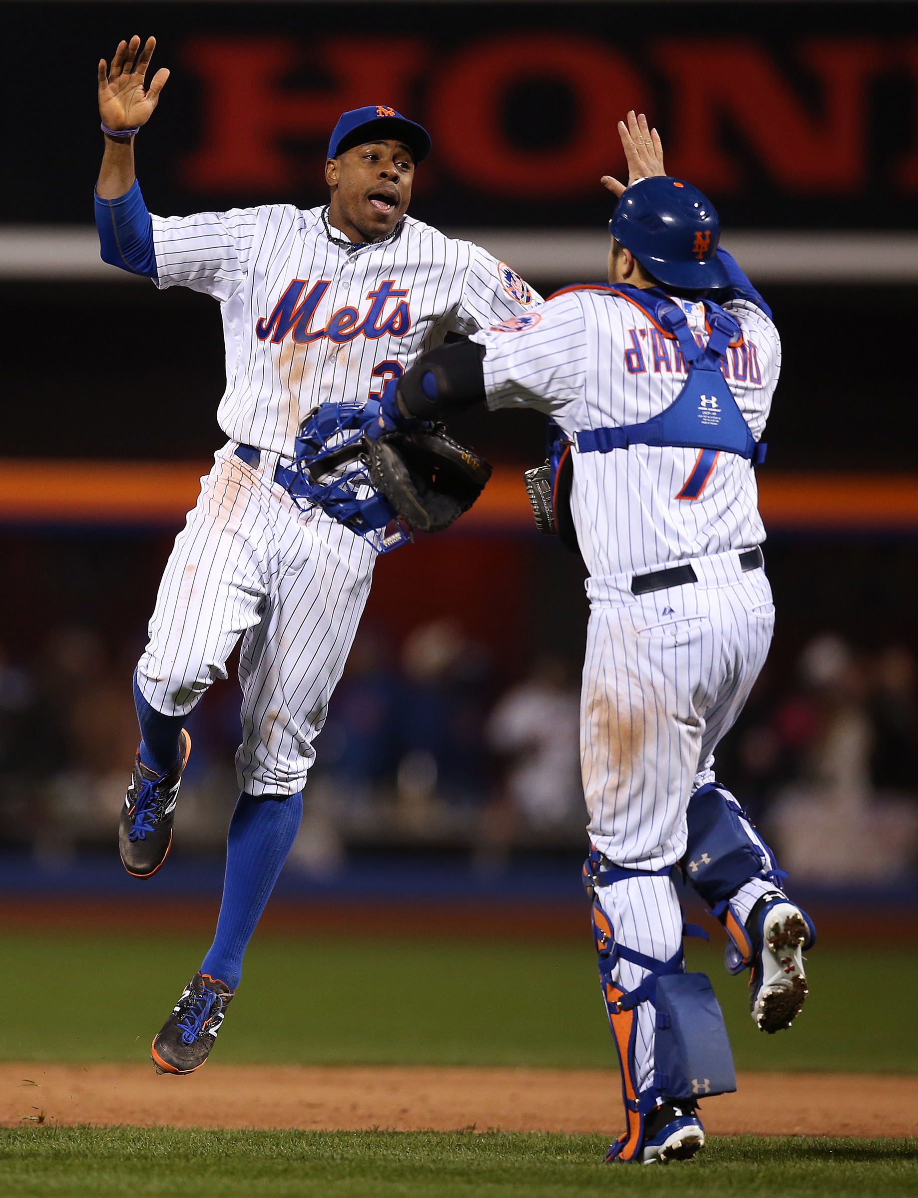 Curtis Granderson #3 and Travis d'Arnaud #7 of the New York Mets celebrate after defeating the Kansas City Royals 9-3 in Game 3 of the 2015 World Series at Citi Field on Friday, October 30, 2015 in the Queens borough of New York City.