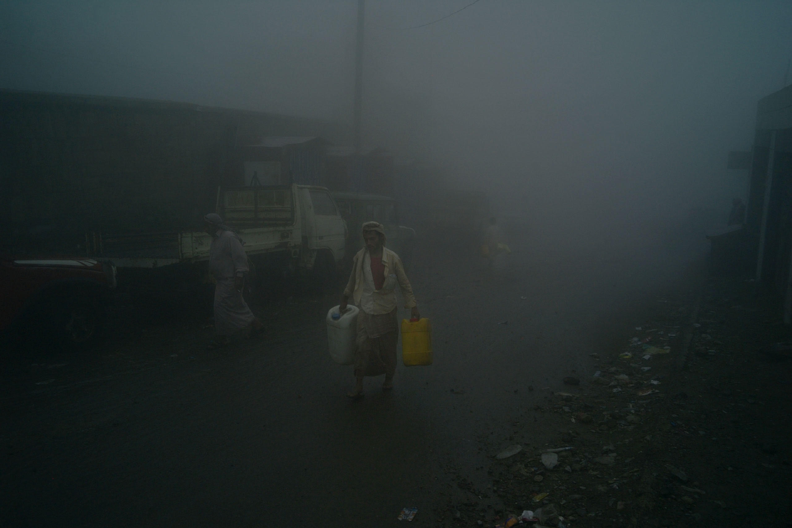 A man carries water in the streets of Hajjah in Yemen's northwestern provinces where civilians struggle for access to safe drinking water since the Saudi-led airstrikes began in March 2015. While international NGO's provide some relief, Yemen faces a severe water crisis resulting in health and sanitation problems, Aug. 2015