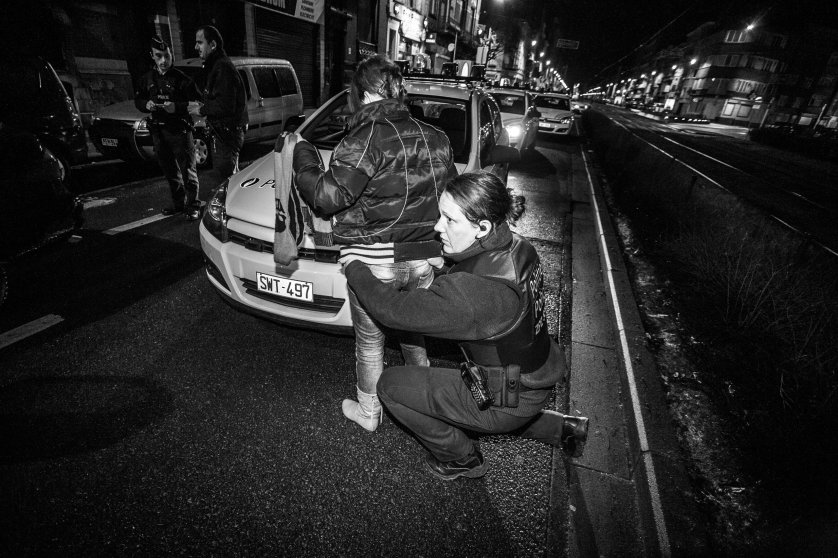 A Police woman search a women in the middle of the street after a call for a street fight. Brussels Ouest ( Molenbeek-Saint-Jean, Koekelberg, Jette, Ganshoren et Berchem-Sainte-Agathe), Belgium on January 28, 2010.