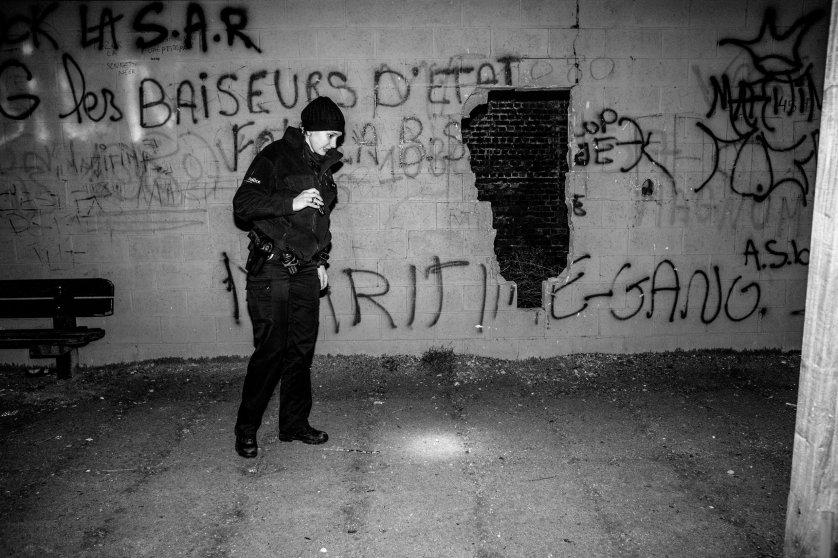 A policewomen searching for evidence in the bad area of Molenbeek, Brussels, Belgium on February 2011