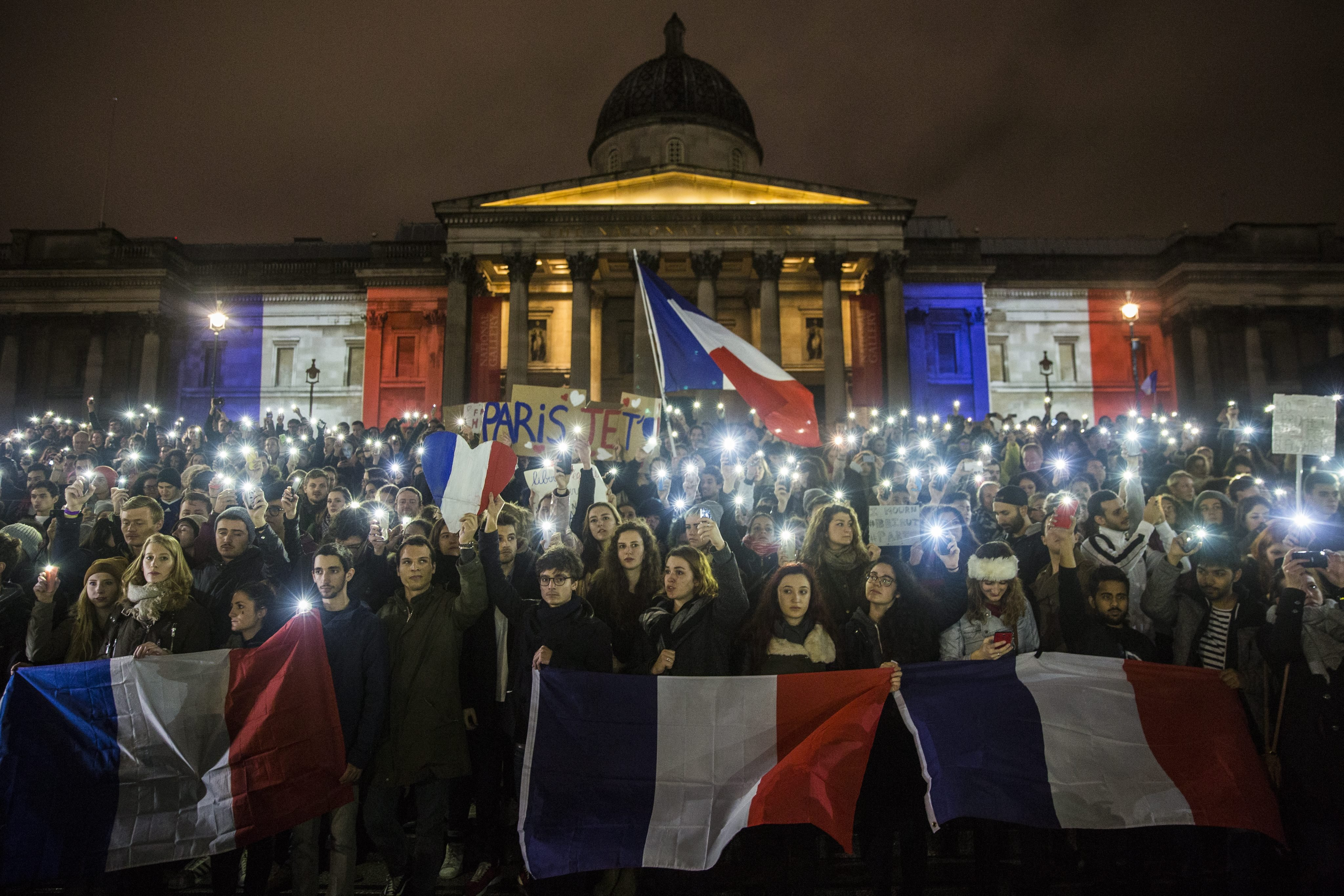 Hundreds of people attend a vigil for the victims of the Paris attacks in Trafalgar Square, central London Nov. 14, 2015.