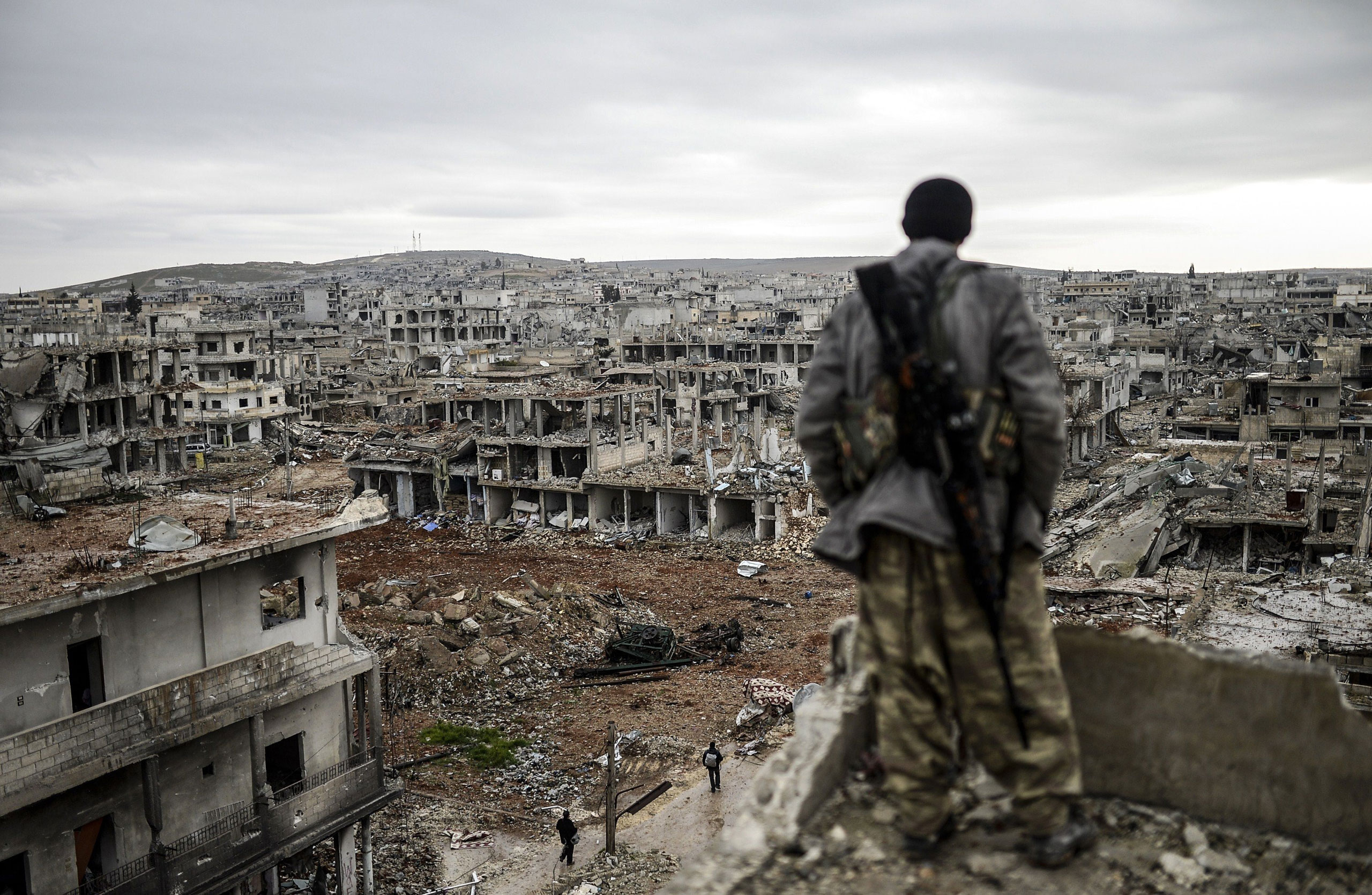 Musa, a 25-year-old Kurdish marksman, stands atop a building as he looks at the destroyed Syrian town of Kobane, also known as Ain al-Arab, on January 30, 2015. Kurdish forces recaptured the town on the Turkish frontier on January 26, in a symbolic blow to the jihadists who have seized large swathes of territory in their onslaught across Syria and Iraq.