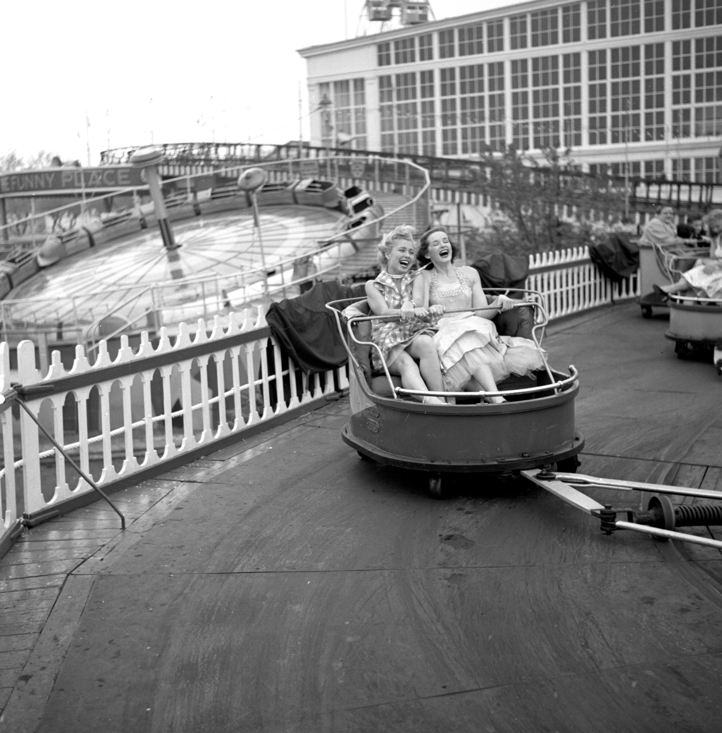 Models from the CBS gameshow,  The Big Payoff,  Cindy Robbins and Pat Conway ride The Whip designed and built by W.F. Mangels Company of Coney Island, at Steeplechase Park. Coney Island, Brooklyn, NY.