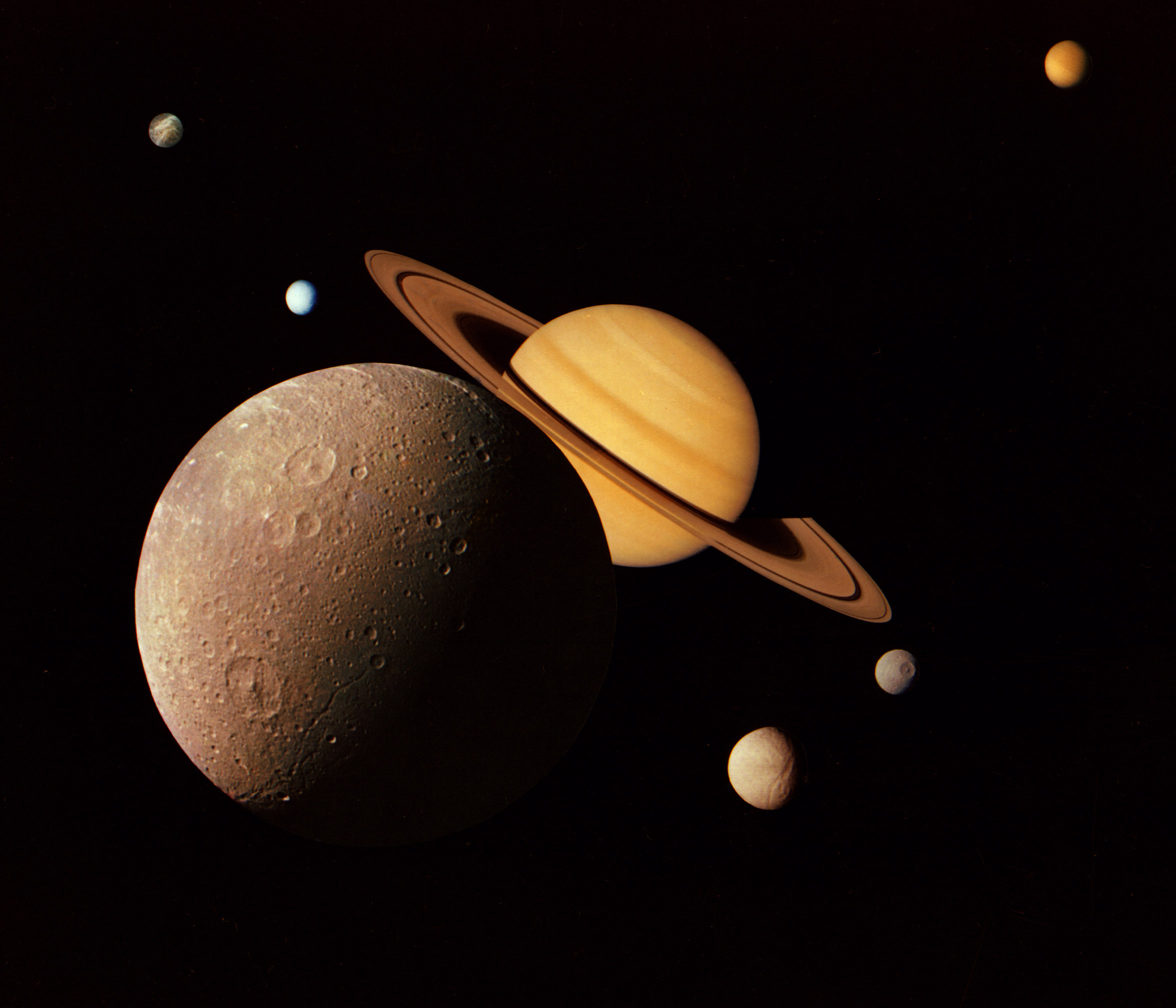 This montage of images of the Saturnian system was prepared from an assemblage of images taken by the Voyager 1 spacecraft during its Saturn encounter in November 1980. This artist's view shows Dione in the forefront, Saturn rising behind, Tethys and Mimas fading in the distance to the right, Enceladus and Rhea off Saturn's rings to the left, and Titan in its distant orbit at the top. The Voyager Project is managed for NASA by the Jet Propulsion Laboratory, Pasadena, California.