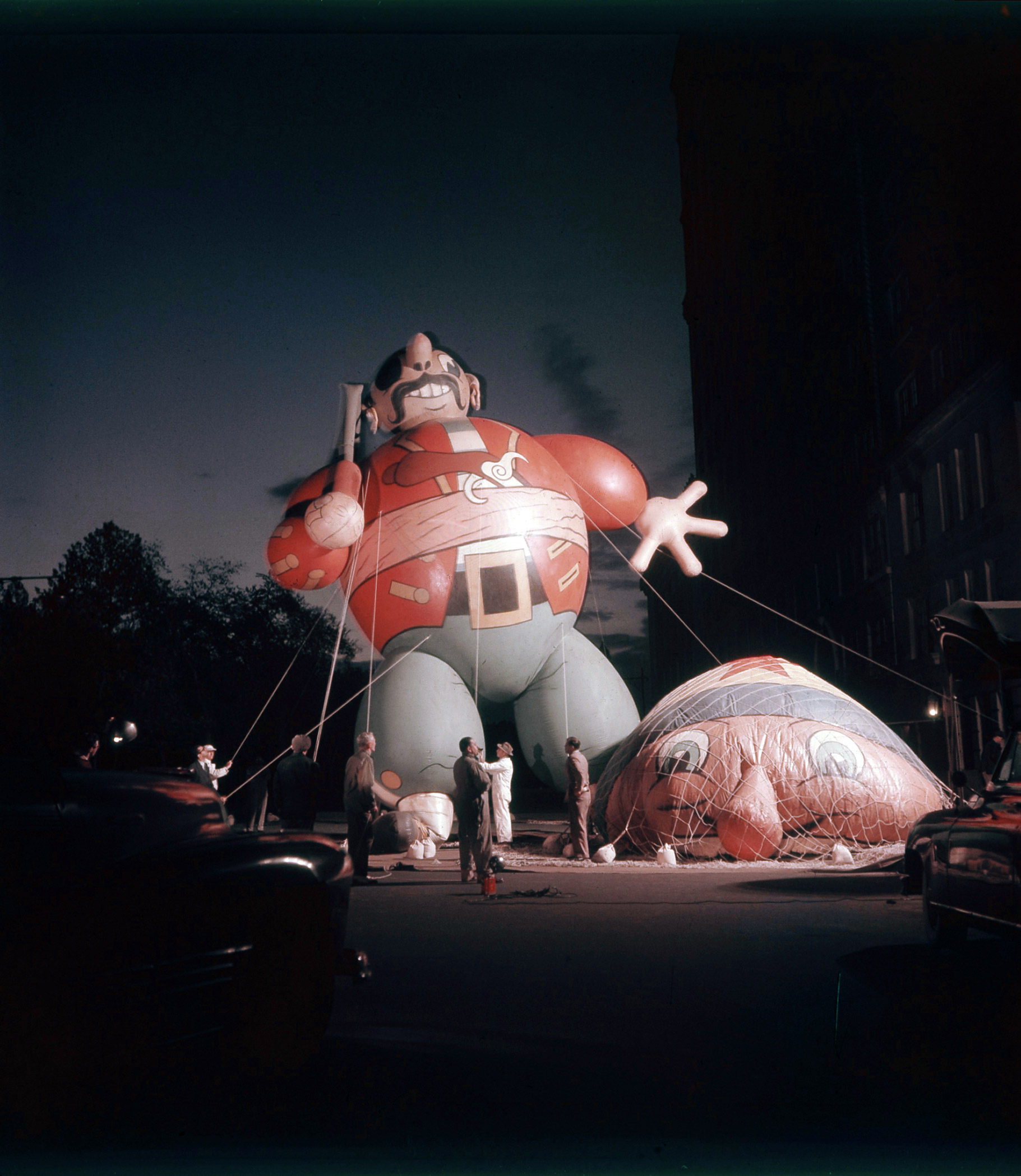 Caption from LIFE. Gigantic balloon figures, the 40-to-75-foot-high trademarks of Macy's Thanksgiving Day parade in New York, are inflated at predawn rehearsal. Six in all, they cost $5,000 to $8,000 each, and they use 50,000 cubic feet of helium. They are occasionally revamped: a cop becomes a fireman, a puritan a pirate.