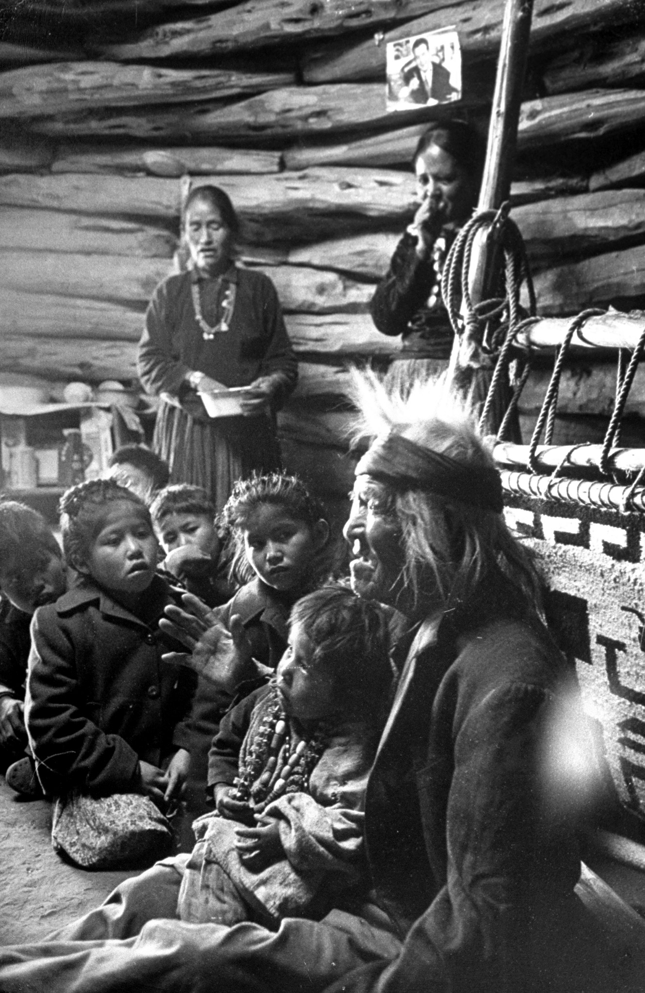 Caption from LIFE. Seated close to the evening fire, old man Gray Mountain, 91, tells his small grandchildren legends about the early days of the Navajo people.