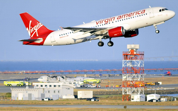 A Virgin America flight takes off while a crashed Asiana Airlines Boeing 777 is seen on the runway at San Francisco International Airport.