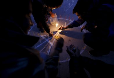 People light candles during a vigil in Kathmandu