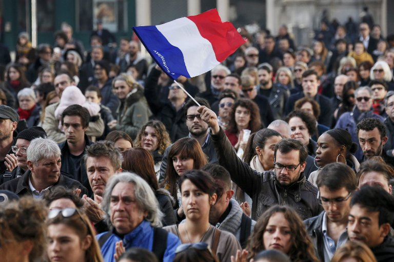 A man waves a French flag as several hundred people gather to observe a minute of silence for the victims of ISIS attacks on Paris in Lyon, France.