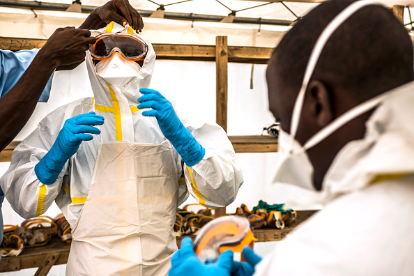 A healthcare worker assists a colleague to dress in Personal Protective Equipment (PPE) at an Ebola Treatment Center in Coyah, Guinea, on Sept. 10, 2015